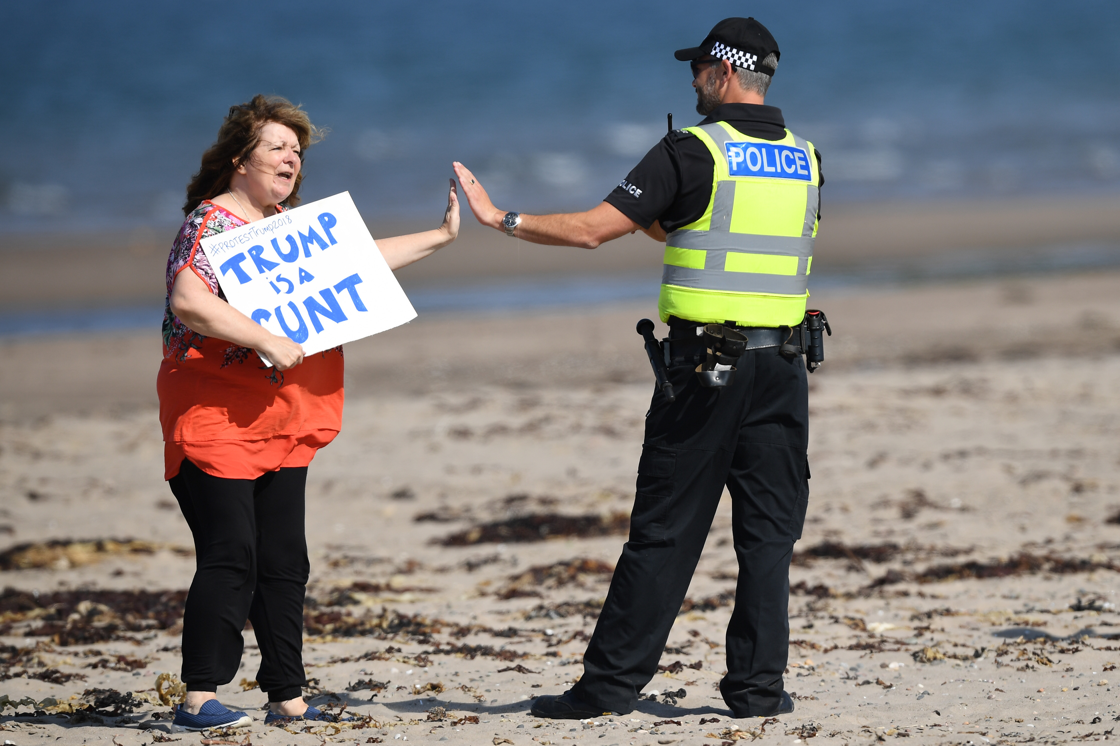 """TURNBERRY, SCOTLAND - JULY 14:  Scottish stand-up comedian Janey Godley gives a high-five to a police officer as she holds a sign in protest stating """"Trump is a runt"""" on the beach outside near Trump Turnberry Luxury Collection Resort during the U.S. President's visit to the United Kingdom on July 14, 2018 in Turnberry, Scotland. The President of the United States and First Lady, Melania Trump on their first official visit to the UK after yesterday's meetings with the Prime Minister and the Queen is in Scotland for private weekend stay at his Turnberry."""