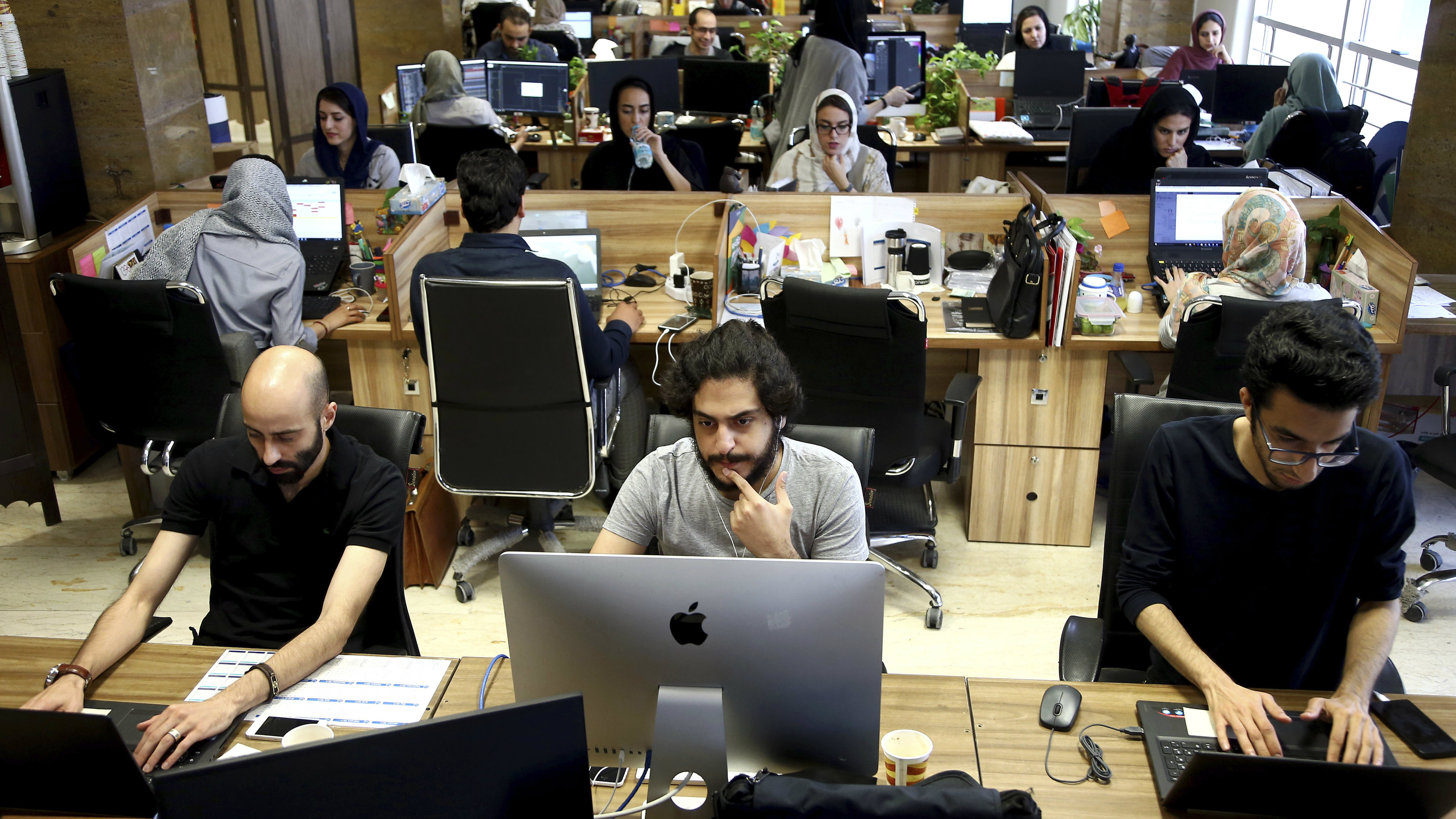 In this Monday, May 23, 2017, photo, staffers of the Snapp online taxi company work at their office in Tehran, Iran. Iran remains in many ways cut off economically from the rest of the world, fueling a surprisingly active local tech startup scene. It's driven by a growing number of Iranian millennials who see their country as a market ripe with opportunity.