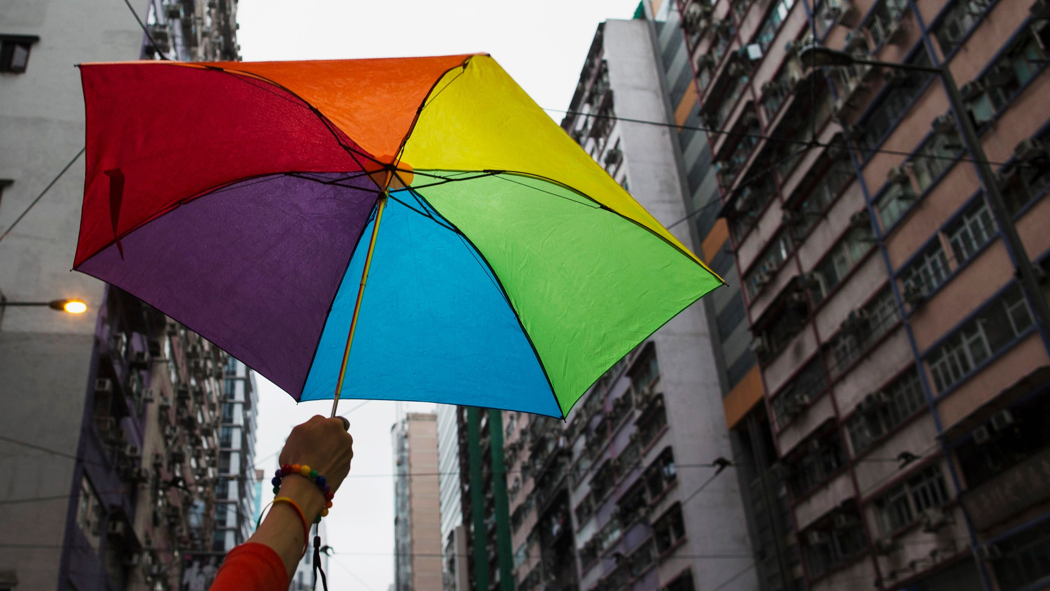 A participant holds a rainbow umbrella as he attends a lesbian, gay, bisexual and transgender (LGBT) Pride Parade in Hong Kong November 8, 2014. Participants from the LGBT communities took to the streets on Saturday to demonstrate for their rights. REUTERS/Tyrone Siu