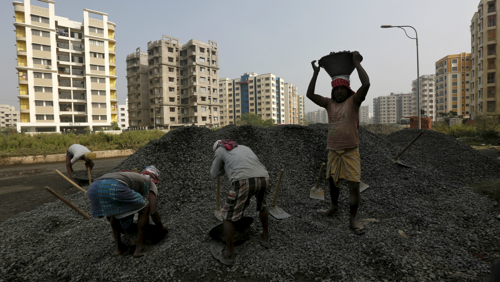 Labourers work at the construction site of a residential complex on the outskirts of Kolkata, India January 23, 2016. India's banks, struggling to boost mainstay corporate loans, are finding a bright spot in a home-buying spree in the country's towns that has driven mortgage-loan growth to the fastest rate in at least six years.