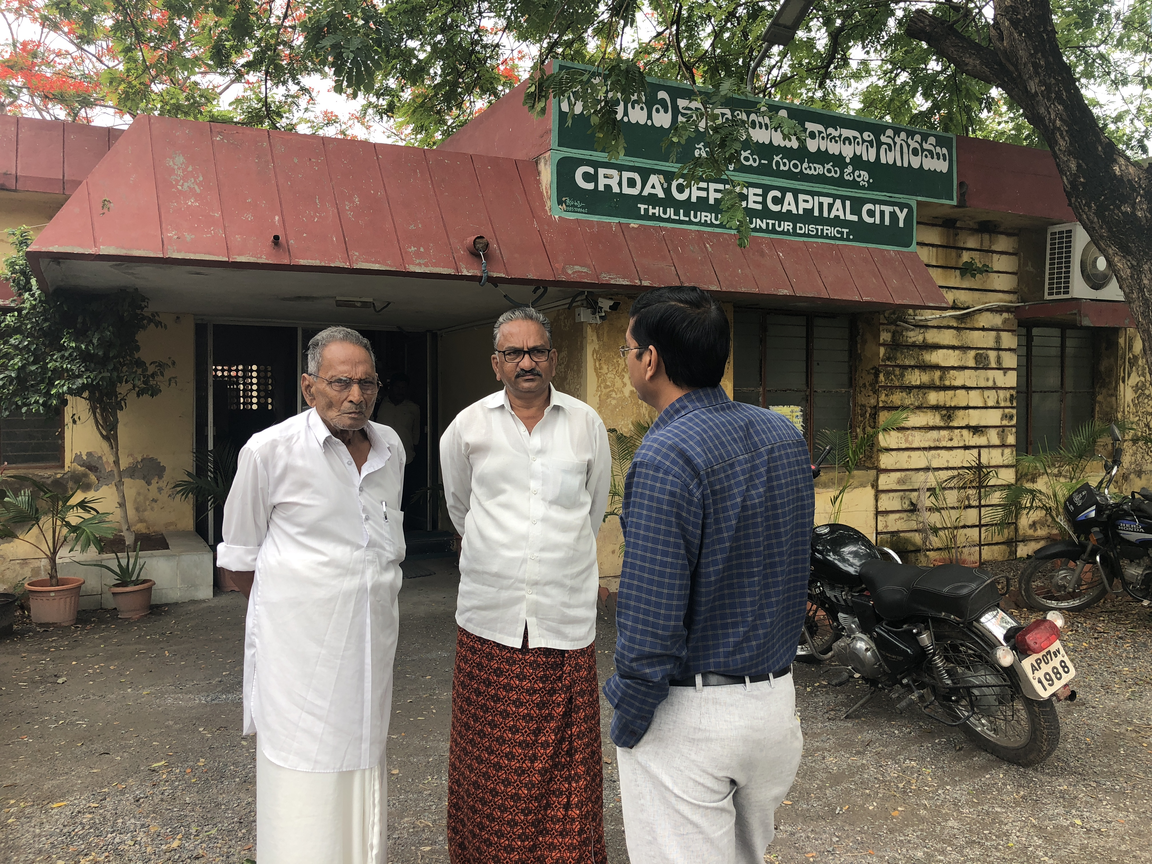 Farmers Kommineni Ramanjaneyulu and Tharigopula Sambasiva Rao talking to PV Suresh Kumar, lead of geographical information systems (GIS) at APCRDA. Photo credit: Quartz/Ananya Bhattacharya