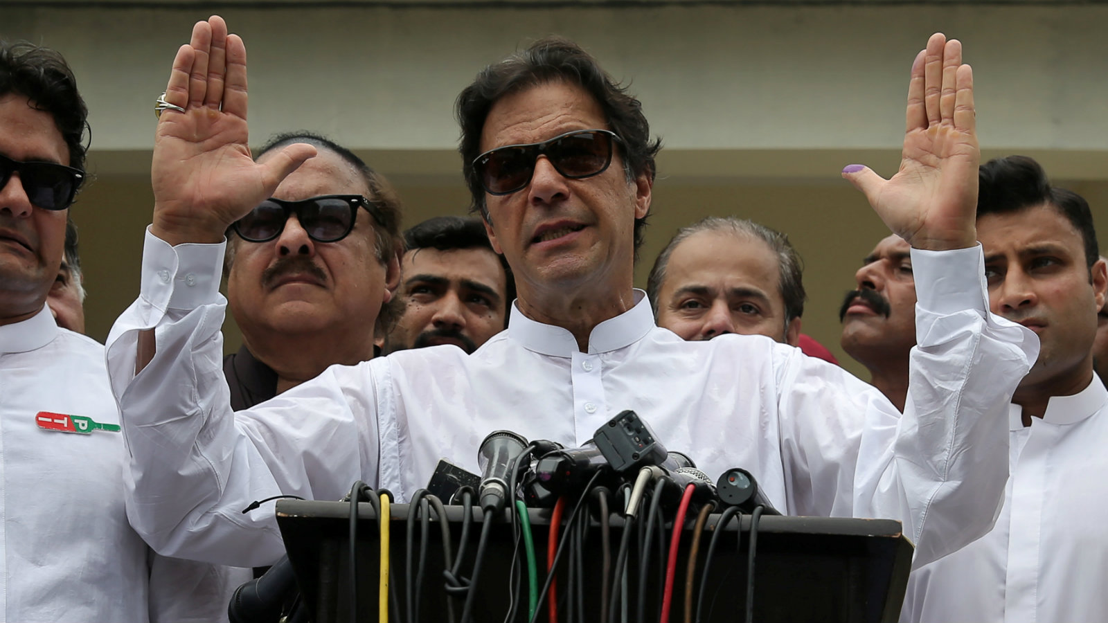 Cricket star-turned-politician Imran Khan, chairman of Pakistan Tehreek-e-Insaf (PTI), speaks to members of media after casting his vote at a polling station during the general election in Islamabad on July 25.