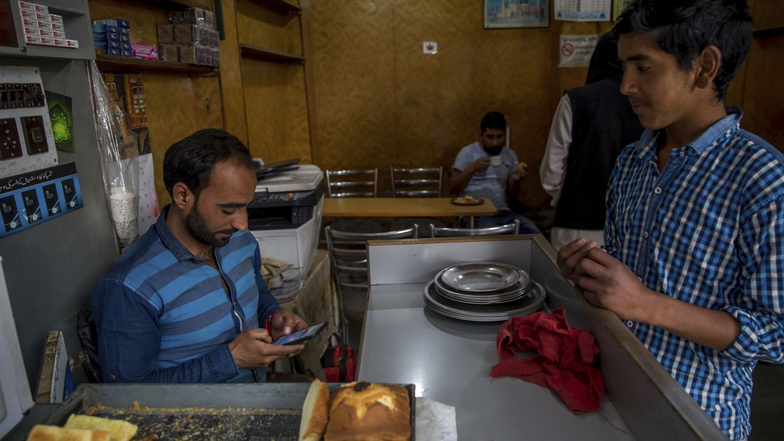 "Kashmiri man Umar Rashid, browses internet on his mobile phone as he sits inside his restaurant in Srinagar, Indian controlled Kashmir, Wednesday, April 26, 2017. On Wednesday, authorities ordered internet service providers to block 16 social media sites, including Facebook and Twitter, and popular online chat applications for one month ""in the interest of maintenance of public order."" The government has often halted internet service in the region in the past in an attempt to prevent anti-India demonstrations from forming. But this is the first time authorities have shut down social media following the circulation    of videos of alleged abuse by Indian soldiers."