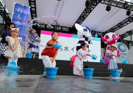Tokyo 2020 Olympic Games mascot Miraitowa, Paralympic mascot Someity and children splash water during an old Japanese tradition called Uchimizu ritual, meant to cool down the air as the water evaporates, prior to a countdown event to mark the two years until the opening of the Olympic Games Tokyo 2020.