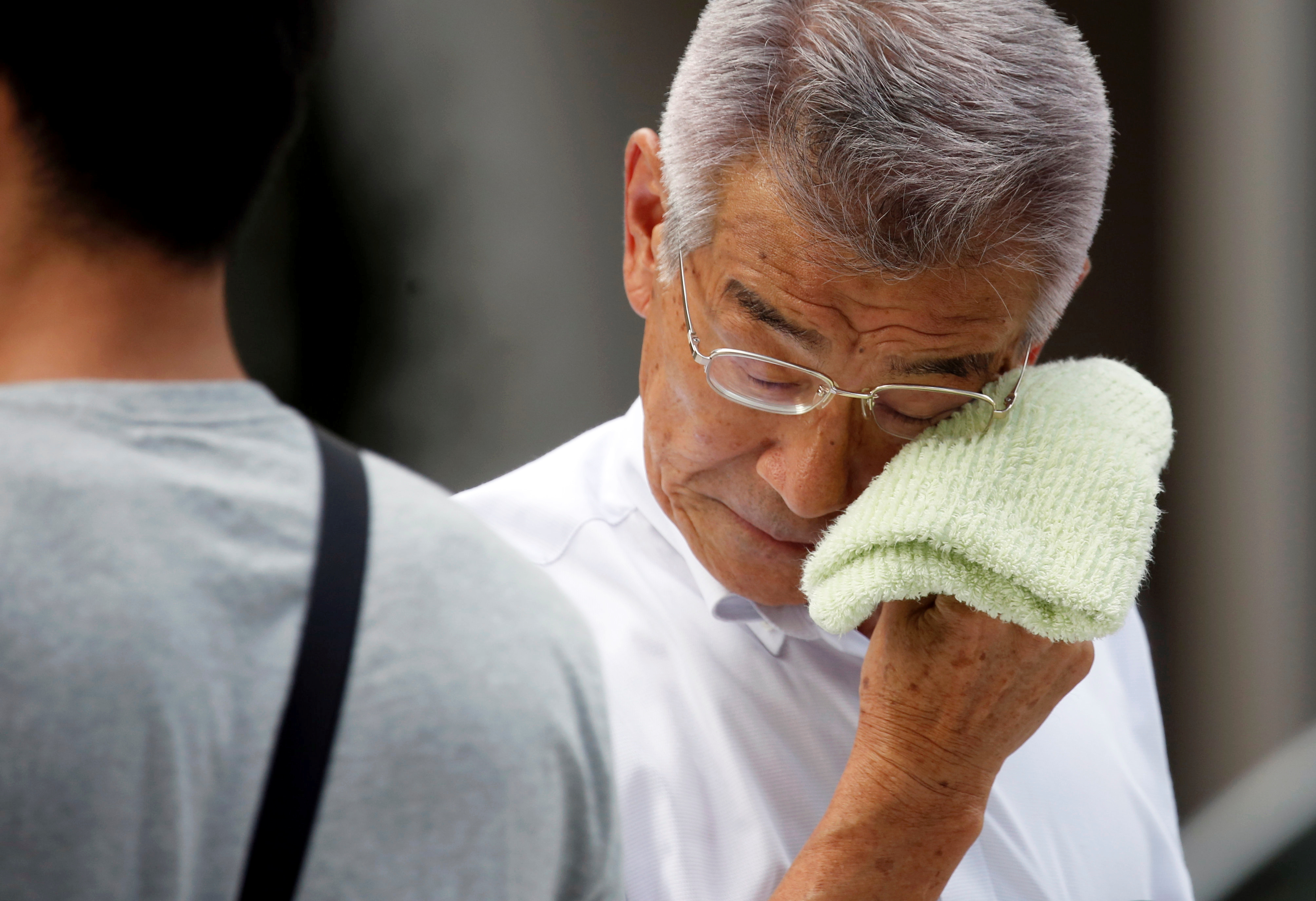 A businessman wipes his face while walking on a street in on Monday.