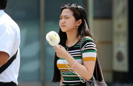 A woman holds a portable fan at a business district in Tokyo, Monday, July 23, 2018. Searing hot temperatures are forecast for wide swaths of Japan and South Korea in a long-running heat wave. The mercury is expected to reach 39 degrees Celsius (102 degrees Fahrenheit) on Monday in the city of Nagoya in central Japan and reach 37 in Tokyo. Deaths have been reported almost every day.