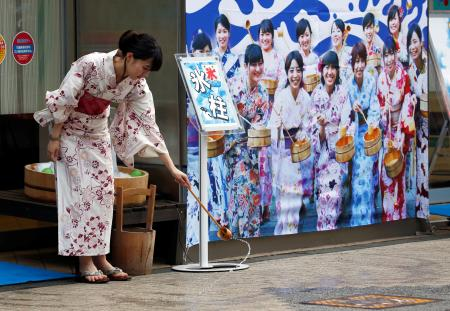 A woman wearing a Yukata, or summer kimono, splashes water onto the hot asphalt in an old Japanese tradition called Uchimizu ritual, meant to cool down the air as the water evaporates, outside a pachinko game parlor in Tokyo.