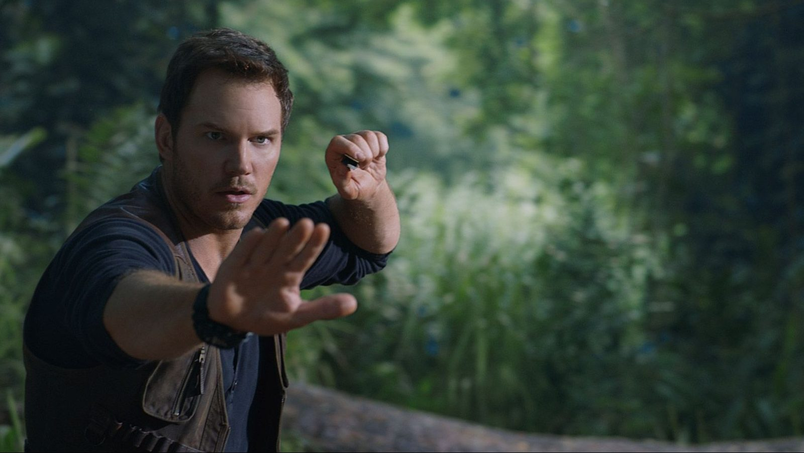 Chris Pratt holds up hand to stop dinosaur