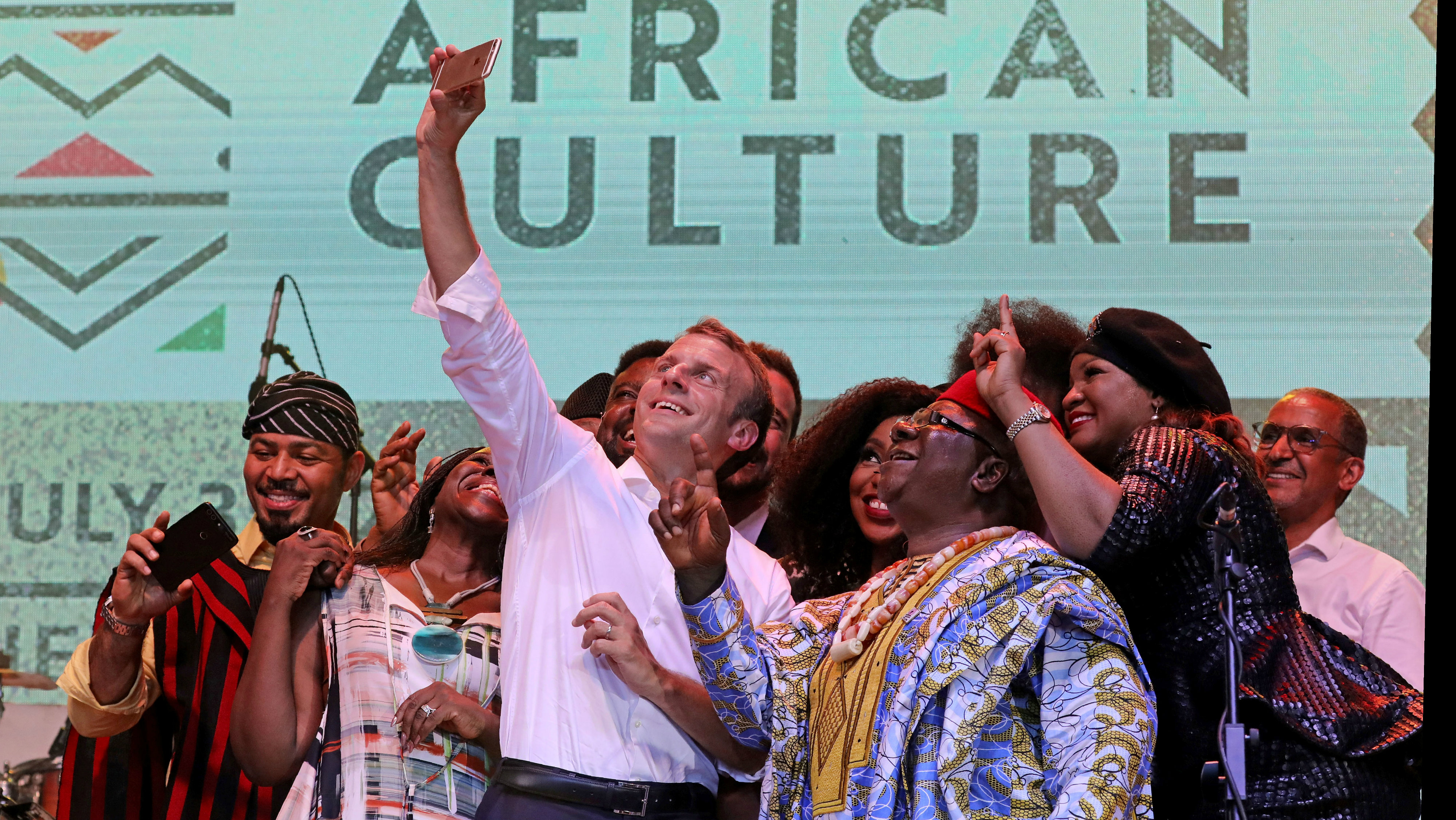 French President Emmanuel Macron (C) takes a selfie with Nollywood artists during a live show in the AfriKa Shrine in Lagos, Nigeria, July 3, 2018. Picture taken July 3, 2018.