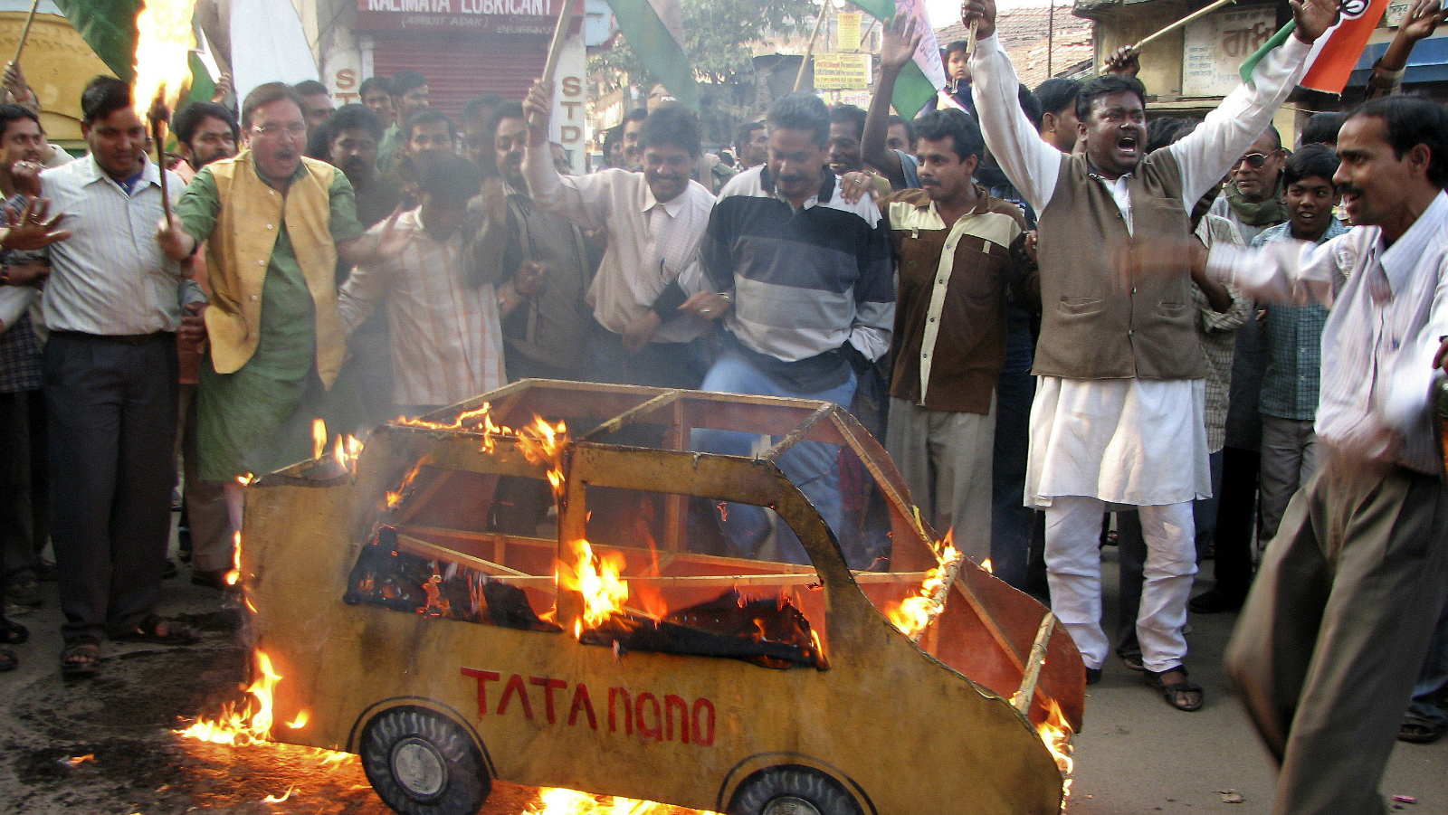 ** TO WITH INDIA TATA ** FILE ** In this Jan. 10, 2007 file photo, activists of Trinamul Congress and Bhumi Raksha Committee burn a replica of Tata Company's newly launched low cost car Nano, near its factory at Singur, about 30 kilometers (20 miles) northwest of Calcutta, India. The 141-year-old Tata company, India's oldest and largest conglomerate whose story is intertwined with that of modern India, is struggling to rally from a string of blows that have left the group drowning in condolence calls, not international applause.