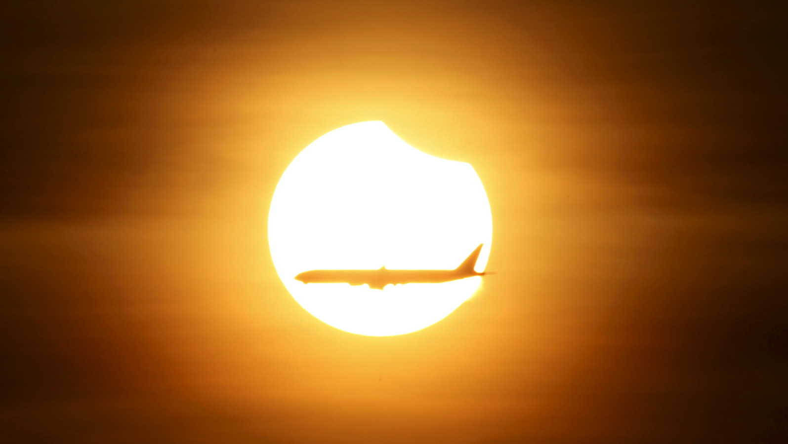 An airplane flying past the sun