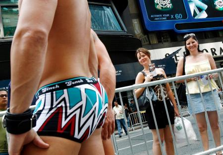 Women look at underwear models in Times Square during Freshpair's National Underwear Day fashion show in New York