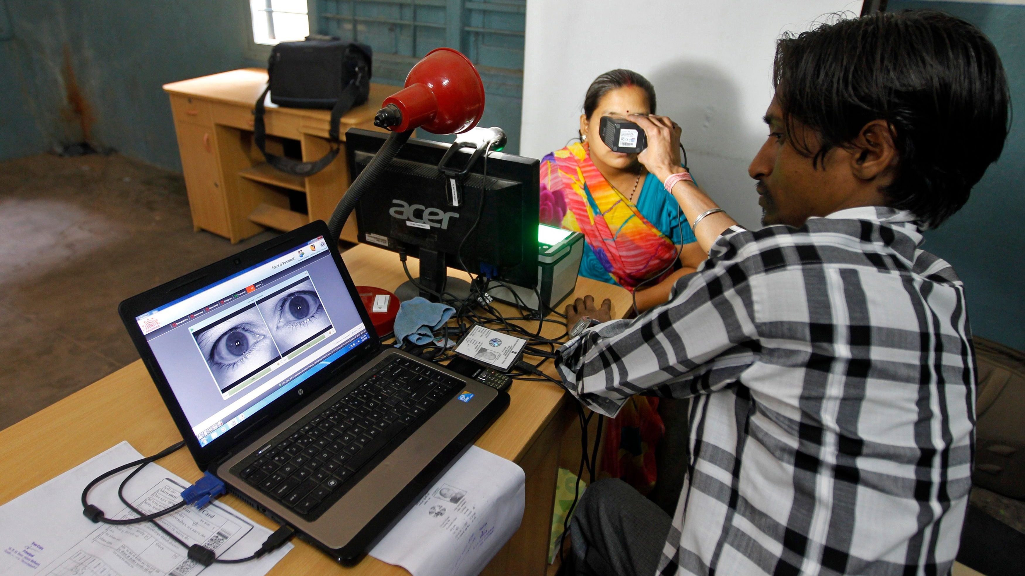 A woman goes through the process of eye scanning for Unique Identification database system in the outskirts of Ahmedabad