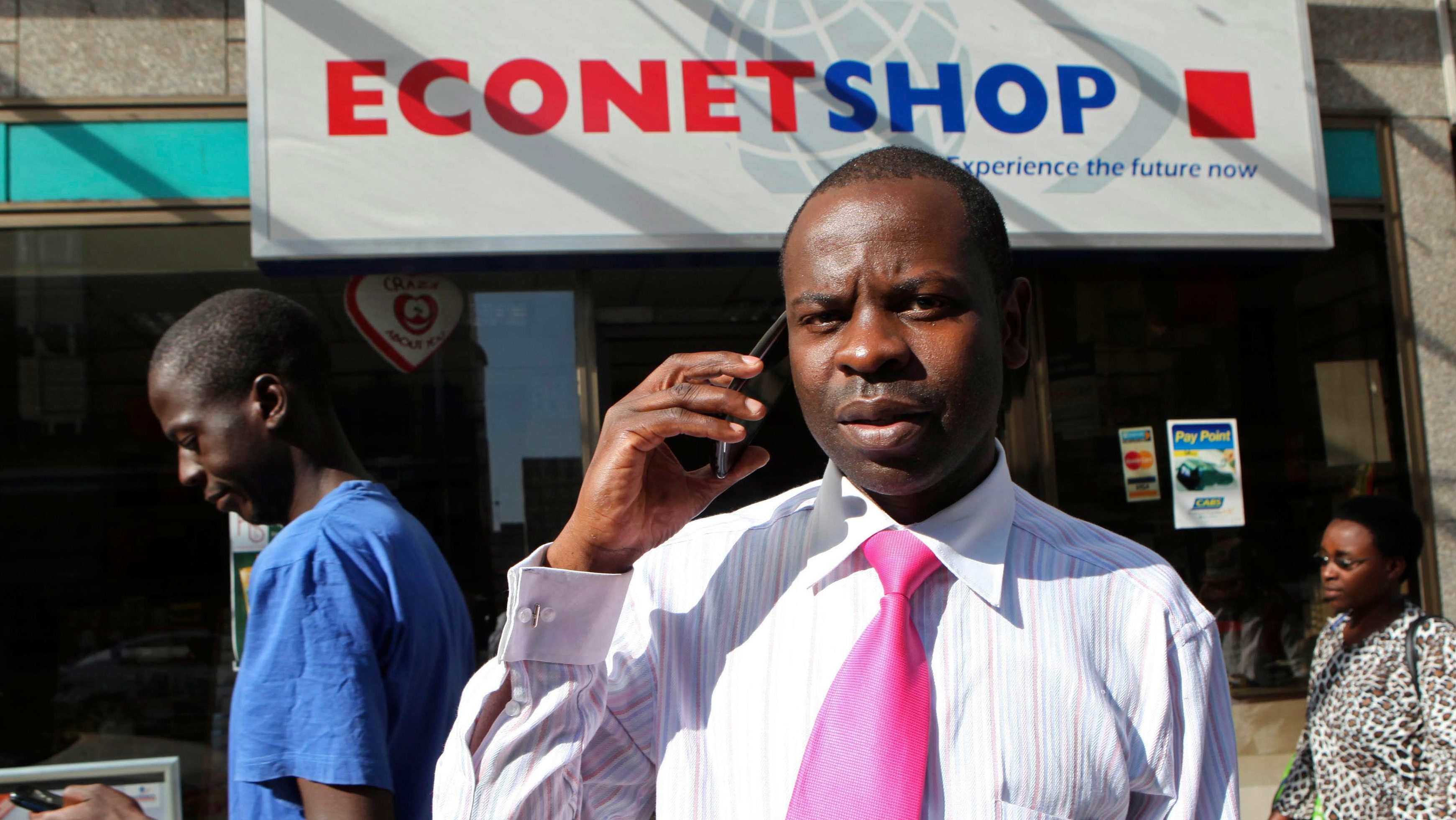 A Zimbabwean man speaks on his phone outside a branch of mobile service provider Econet Wireless in central Harare