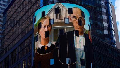 "A reproduction of the art work ""American Gothic"" is displayed on a digital billboard in Times Square,"