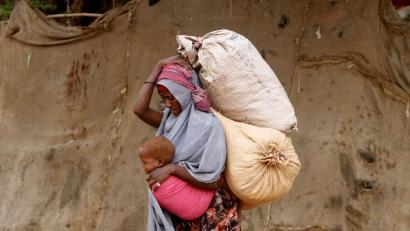 A displaced Somali woman carries a child and her belongings as she arrives at a temporary dwelling after fleeing famine in the Marka Lower Shebbele regions to the capital Mogadishu, September 20, 2014. The United Nations said this month more than a million people in war-ravaged Somalia were struggling to meet daily nutritional needs. The roughly 130,000 people displaced from their homes this year alone are bearing the brunt of the crisis.