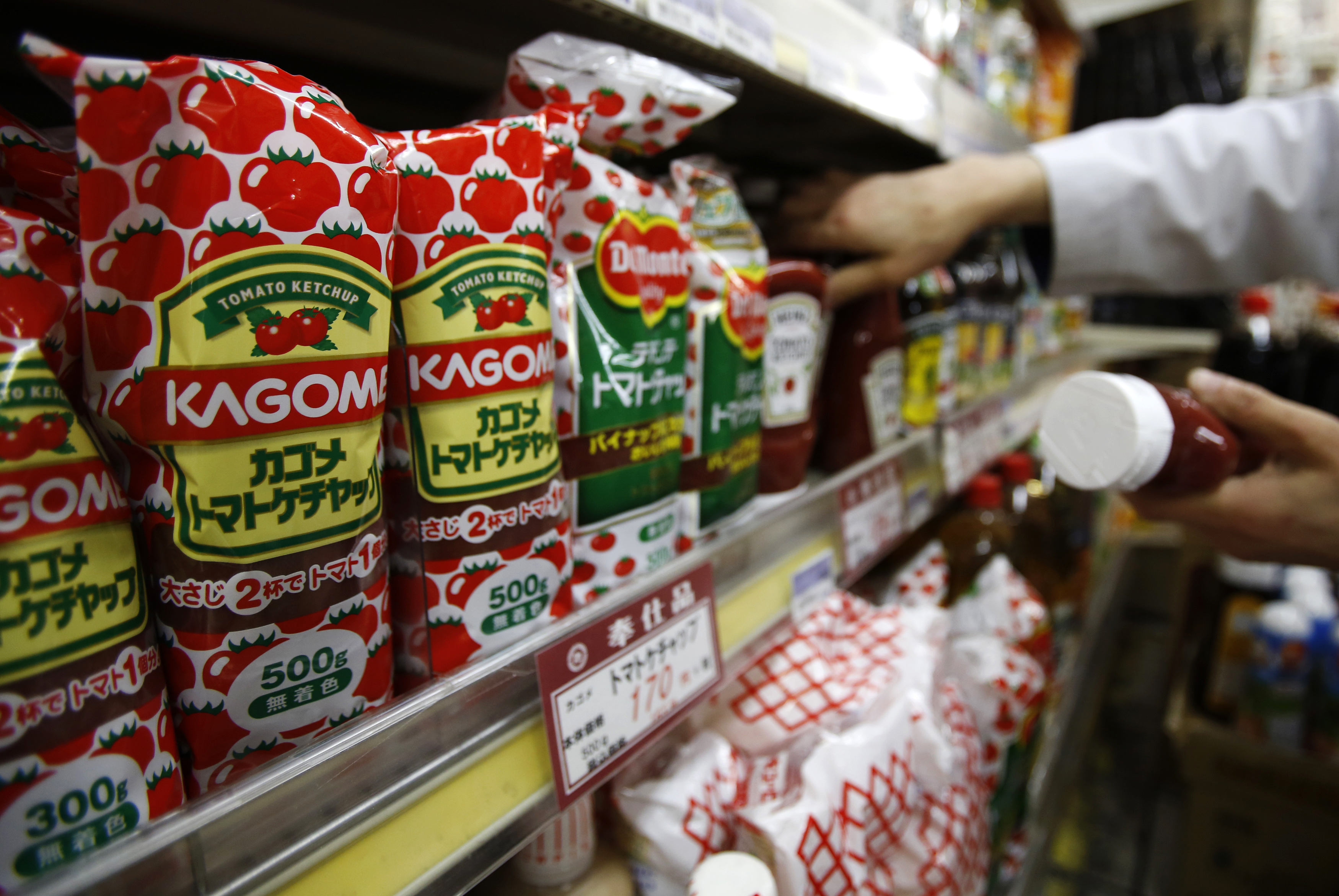 Kagome's tomato ketchup bottles are displayed with their price tag as a staff arranges tomato ketchup bottles of other brands at Yoshiike supermarket in Tokyo