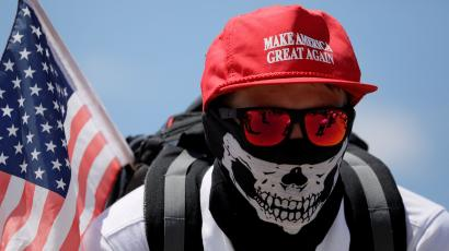 """A masked demonstrator in a Donald Trump """"Make America Great Again"""" hat listens to speeches as self proclaimed """"White Nationalists"""", white supremacists and """"Alt-Right"""" activists gather for what they called a """"Freedom of Speech"""" rally at the Lincoln Memorial"""