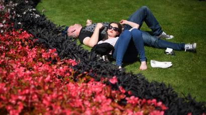 A man and a woman sleep on the grass, on a sunny day in Hyde Park, London