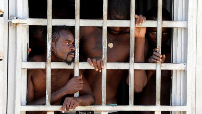 Migrants look out of a barred door at a detention center in Gharyan, Libya October 12, 2017.