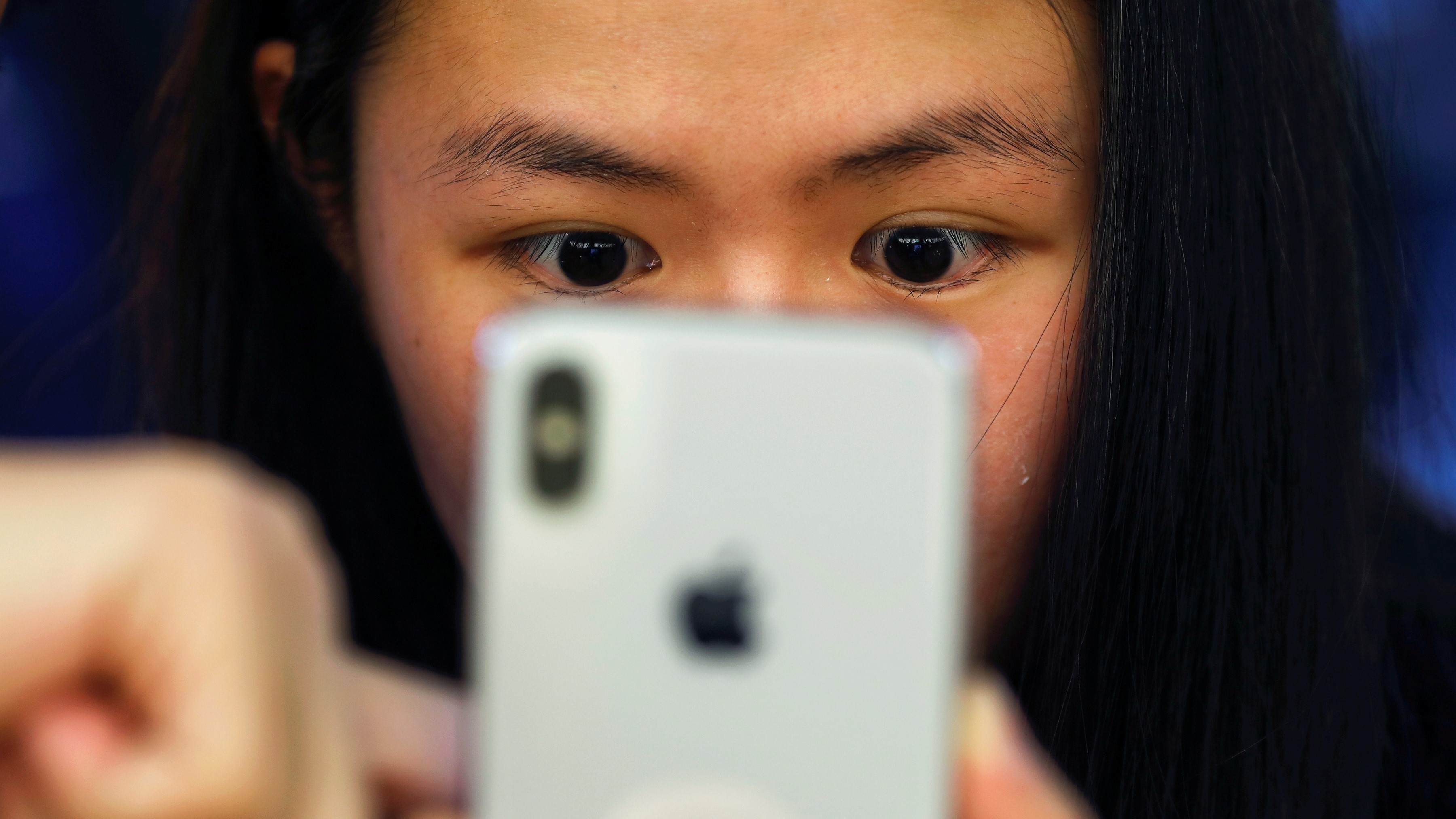 FILE PHOTO: A customer is shown a new iPhone X at an Apple Store in Beijing, China November 3, 2017. REUTERS/Damir Sagolj/File Photo - RC1D6581CBF0