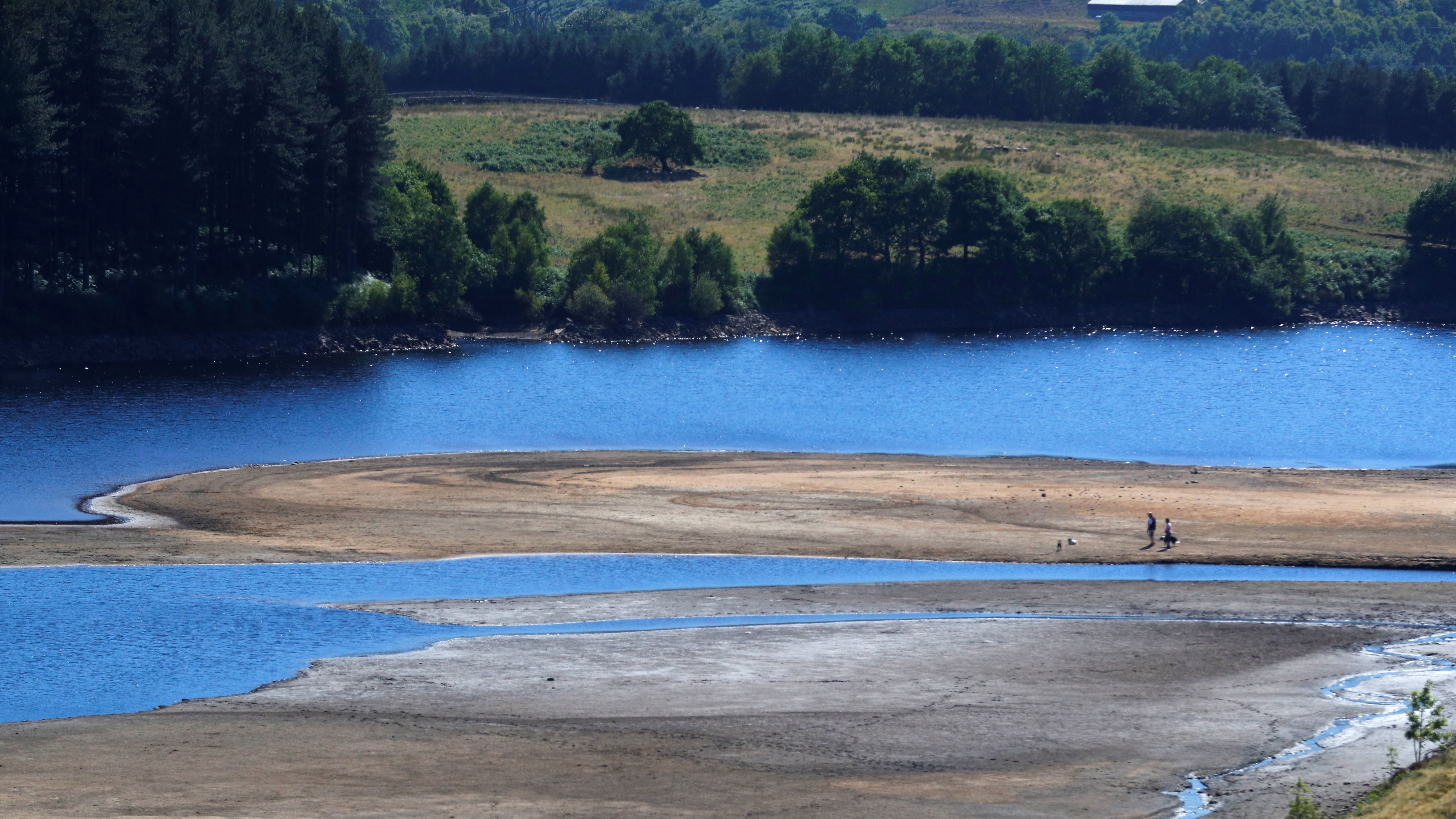 Two people take a walk by the water's edge, where the water level has dropped significantly during the U.K. heatwave, of Torside Reservoir in Longdendale, Derbyshire, Britain, July 3, 2018.  - RC1AB3645B10