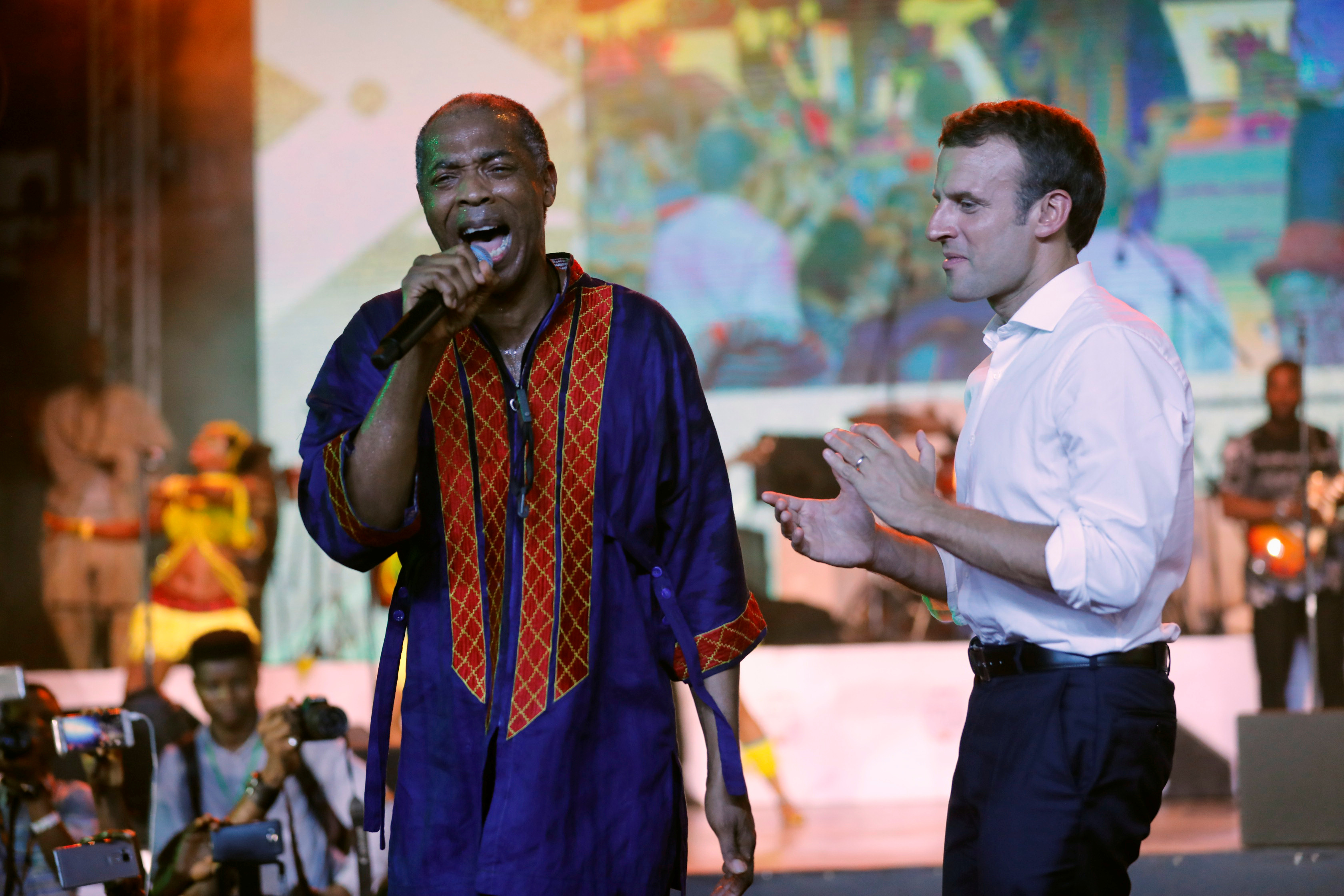 French President Emmanuel Macron (R) stands on stage as Nigerian musician Femi Kuti performs during Macron's visit to the Afrika Shrine nightclub in Nigeria's commercial capital Lagos, July 3, 2018.Picture taken July 3, 2018.