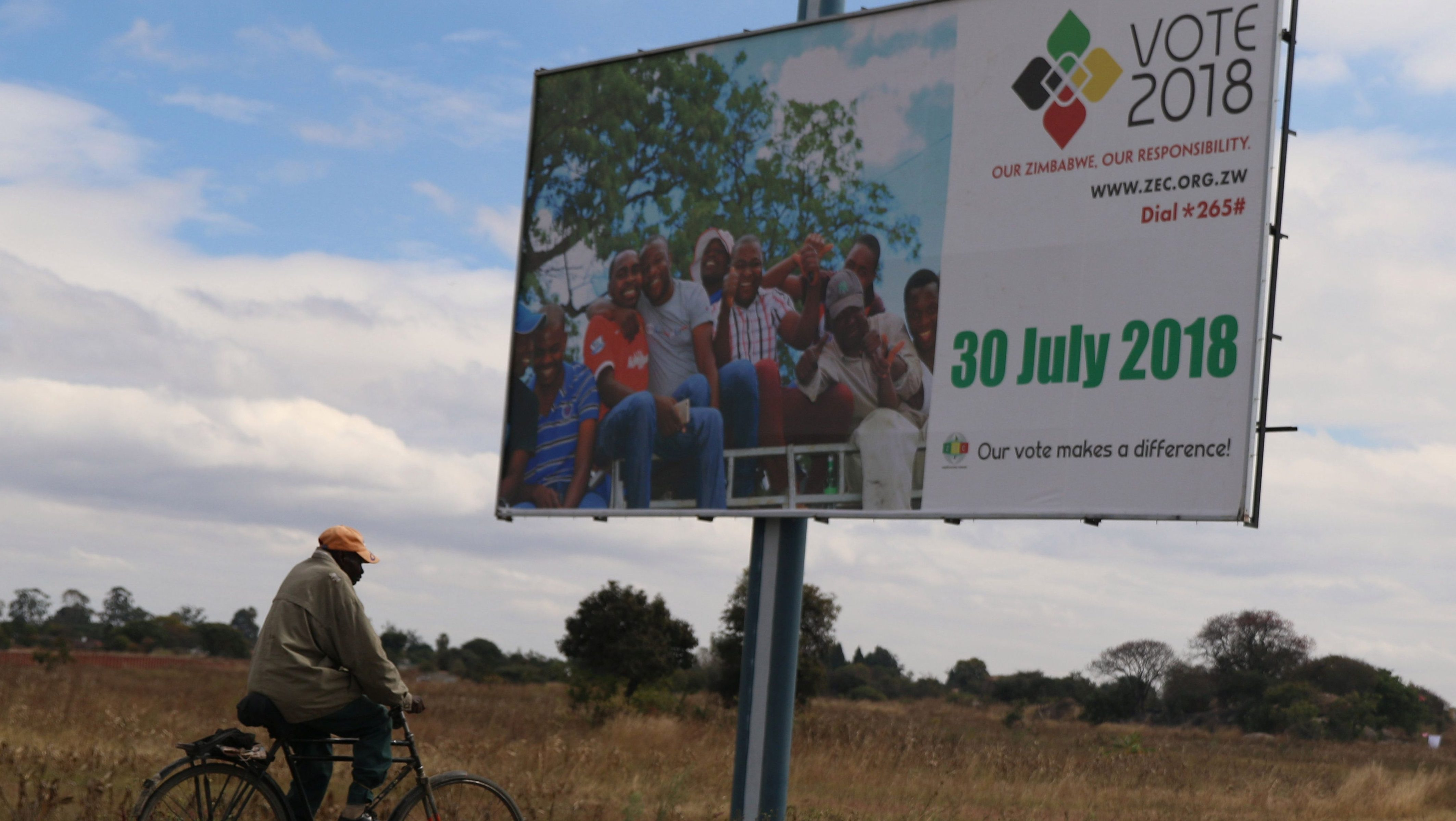A man cycles past an election billboard in Harare
