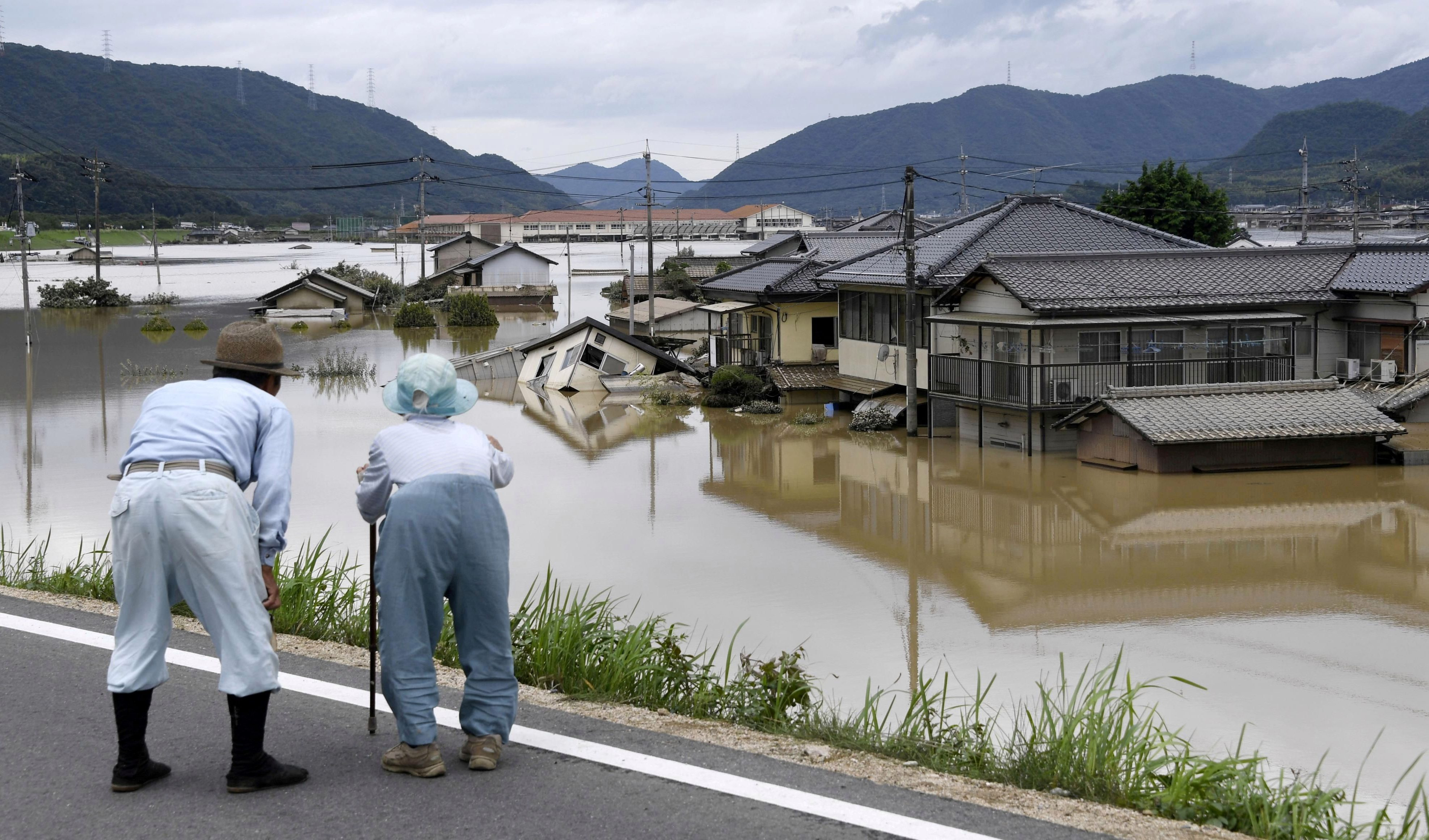 An elderly couple looks at a flooded area after heavy rain in Kurashiki, Okayama Prefecture, Japan, in this photo taken by Kyodo July 8, 2018. Mandatory credit Kyodo/via REUTERS ATTENTION EDITORS - THIS IMAGE WAS PROVIDED BY A THIRD PARTY. MANDATORY CREDIT. JAPAN OUT. NO COMMERCIAL OR EDITORIAL SALES IN JAPAN.     TPX IMAGES OF THE DAY - RC1BF4D778A0
