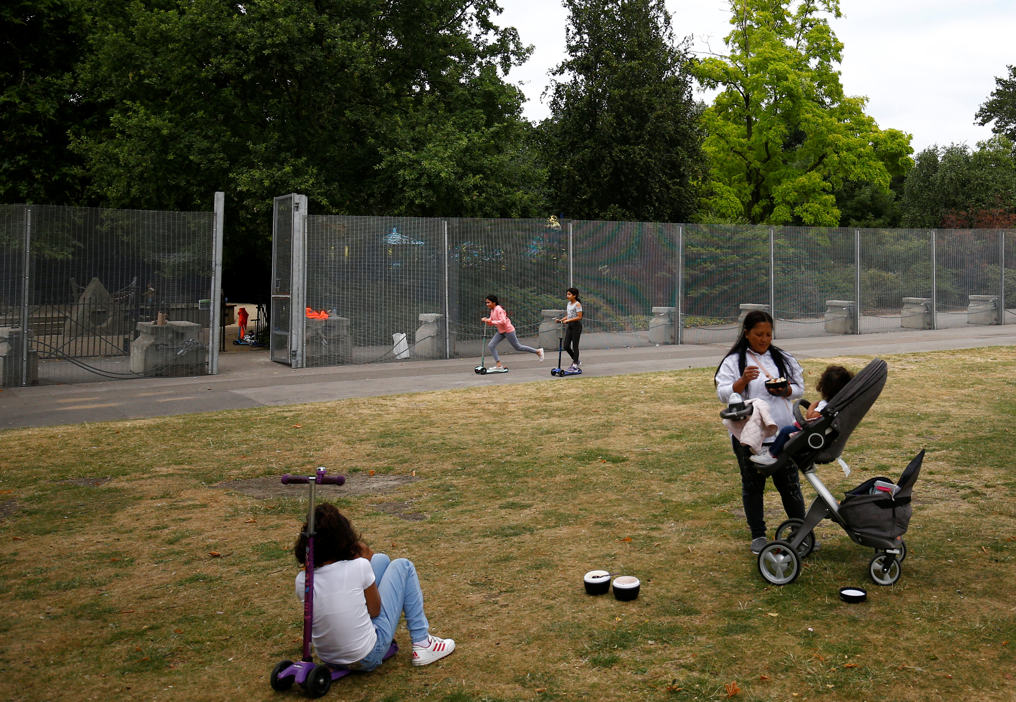 Visitors to the park use a special gate to pass through fences, that have been erected before the U.S. presidential visit at the end of the week, around the U.S. ambassador's residence in Regent's Park in London, Britain, July 10, 2018. REUTERS/Henry Nicholls - RC17948966D0