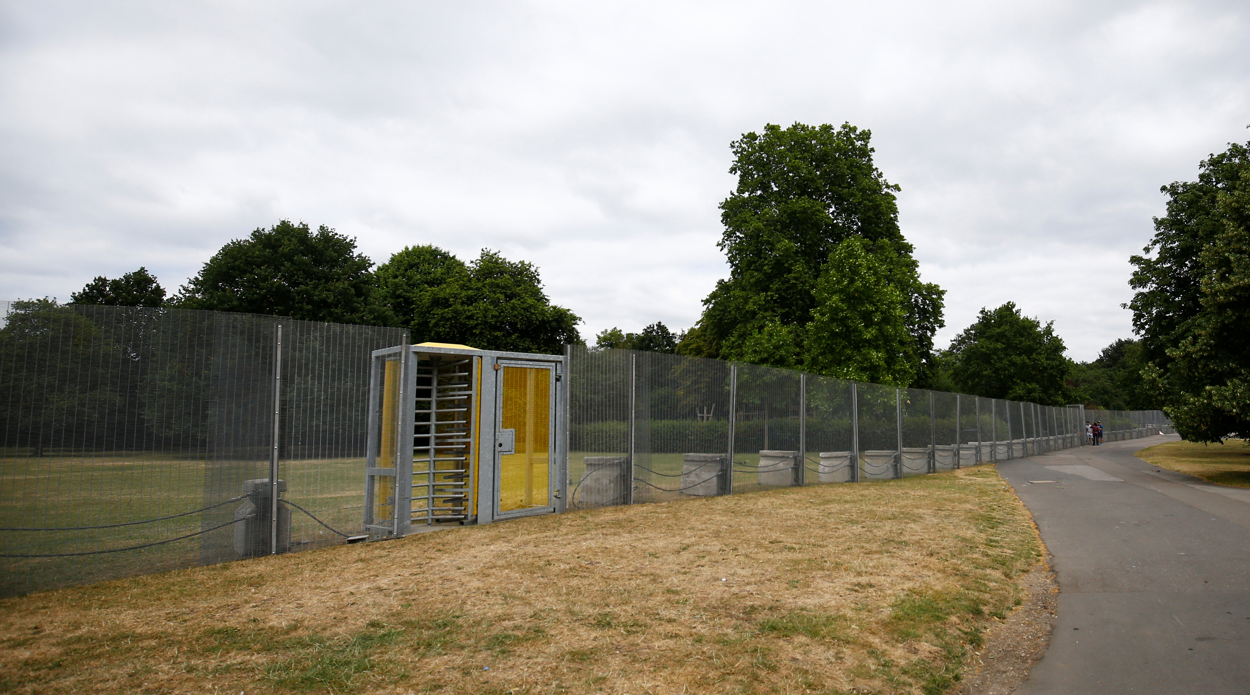 Visitors to the park use a special gate to pass through fences, that have been erected before the U.S. presidential visit at the end of the week, around the U.S. ambassador's residence in Regent's Park in London, Britain, July 10, 2018. REUTERS/Henry Nicholls - RC162E9F4960