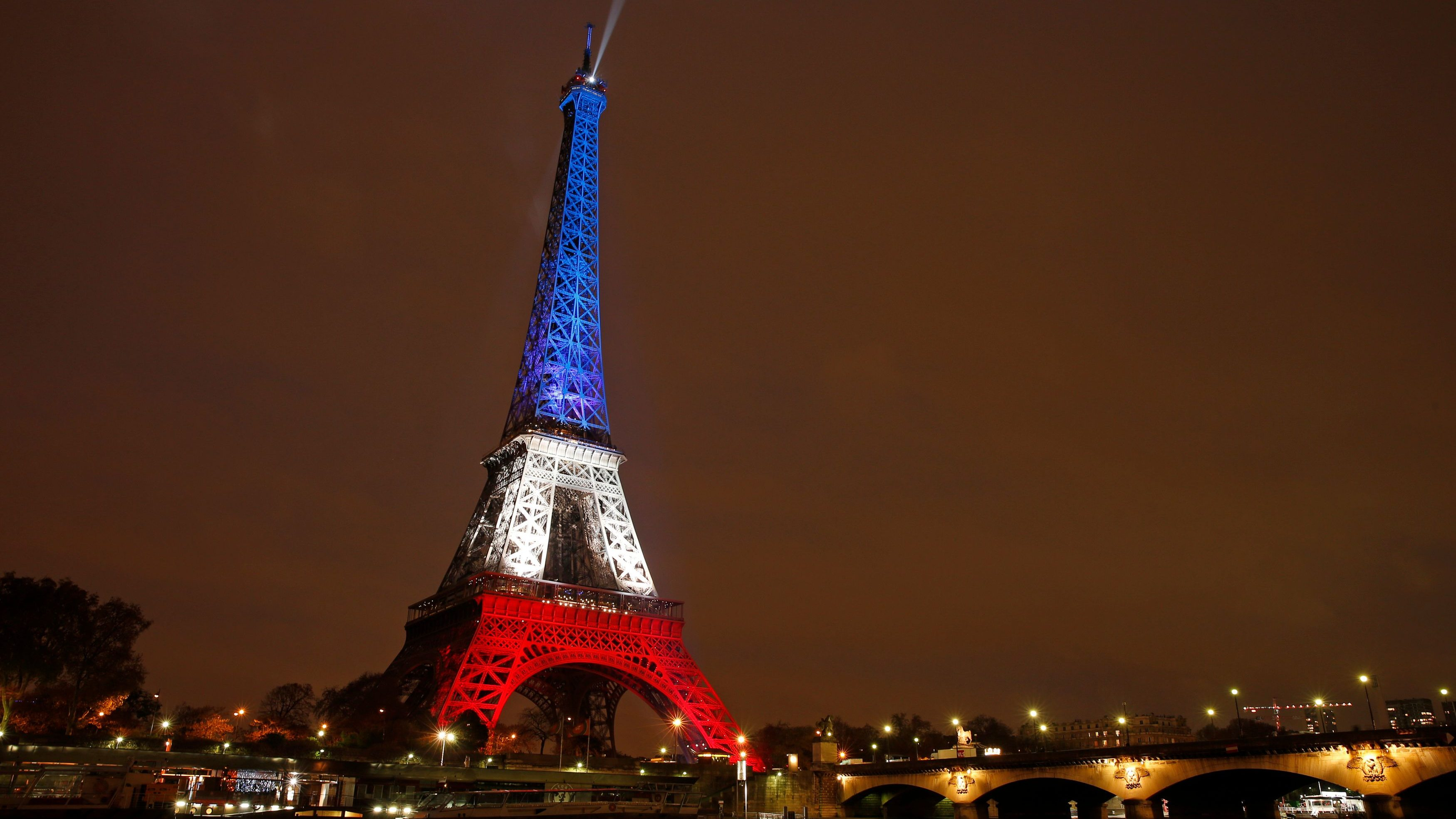 The Eiffel Tower is lit with the blue, white and red colours of the French flag in Paris to pay tribute to the victims of a series of deadly attacks in the French capital