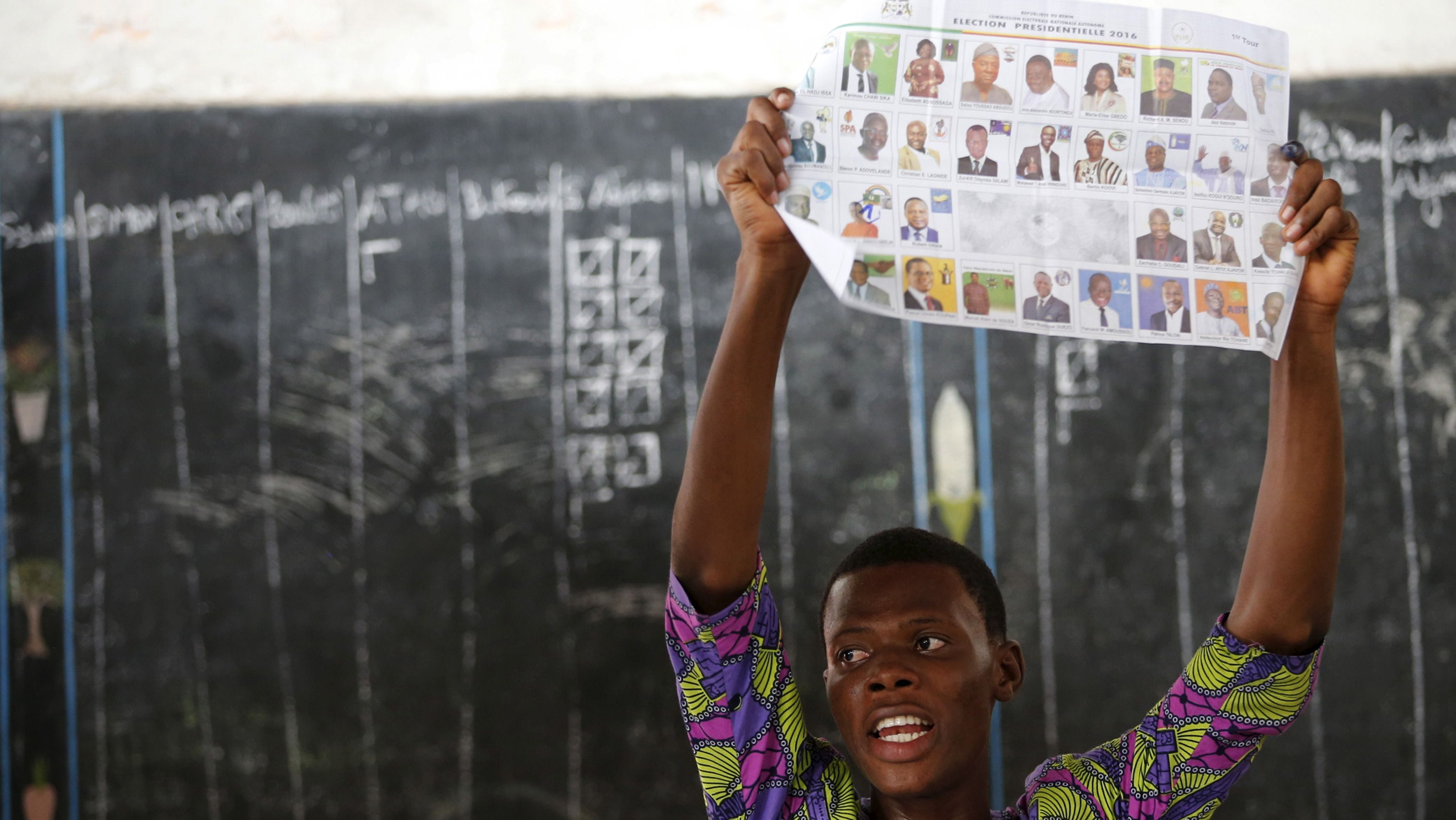An electoral officer holds up a ballot paper during the count of votes after polling stations closed for the presidential election in Cotonou, Benin March 6, 2016.