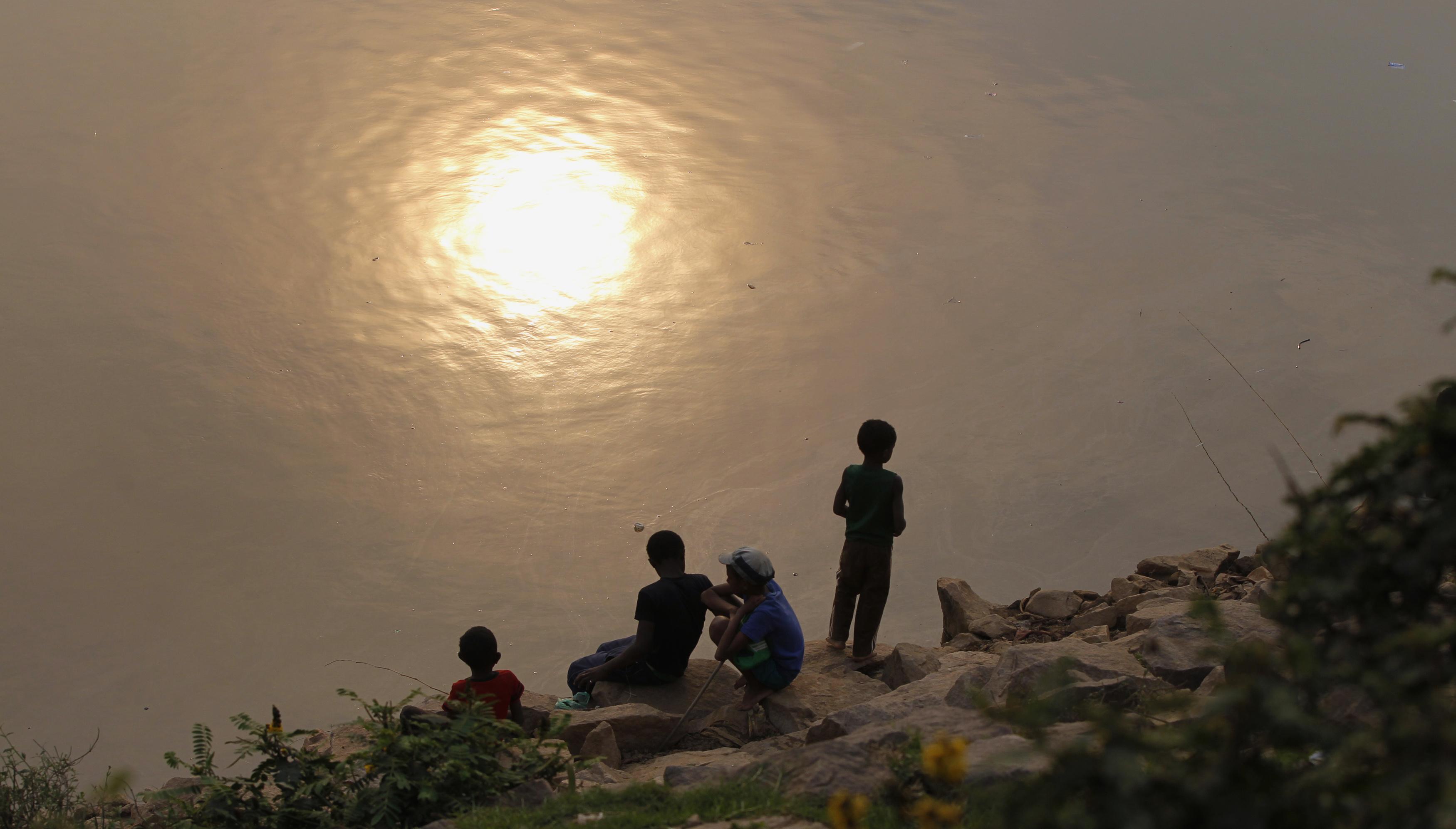 Boys fish at sunset along the banks of the Ikopa river in Madagascar's capital Antananarivo