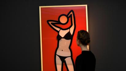 A museum worker poses as she looks at a lenticular print during a media event to promote 'Undressed: A Brief History of Underwear' at the V&A Museum in London