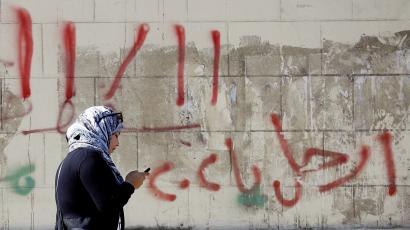 "A woman walks and speaks on her mobile phone in front of a wall with graffiti asking Egyptians to participate in demonstrations against the Egyptian regime and against economic conditions following the rise of prices around the country ,in Cairo, Egypt November 9, 2016. The words read, ""Leave ya Sisi"". Picture taken November 9, 2016."