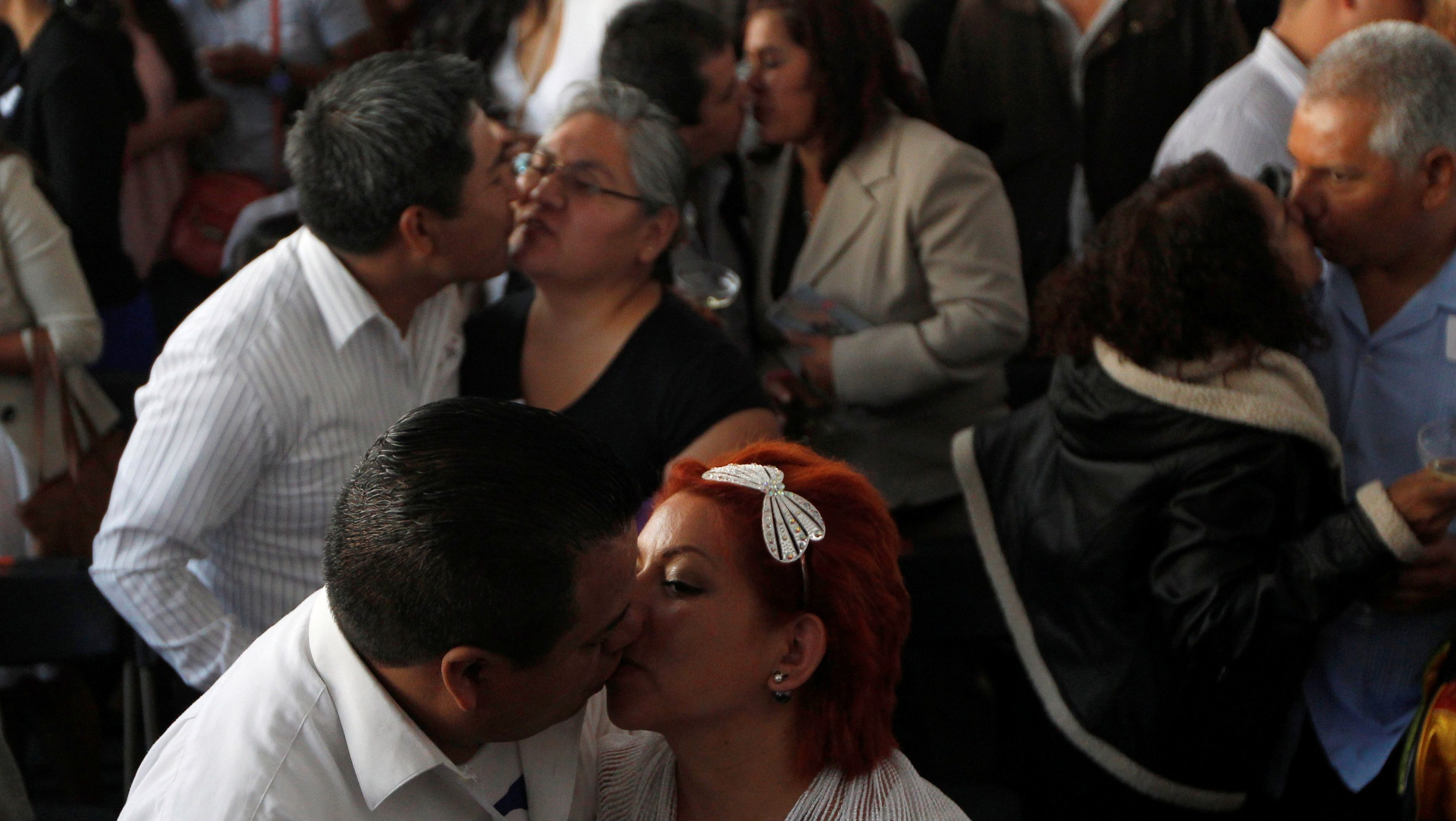 Newly-wed couples kiss during a mass wedding ceremony in which 3,400 couples participated, at Zocalo square in Mexico City, Mexico March 25, 2017.