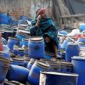 A worker speaks on his phone as he sits on chemical containers near a wholesale market on a winter morning in Kolkata