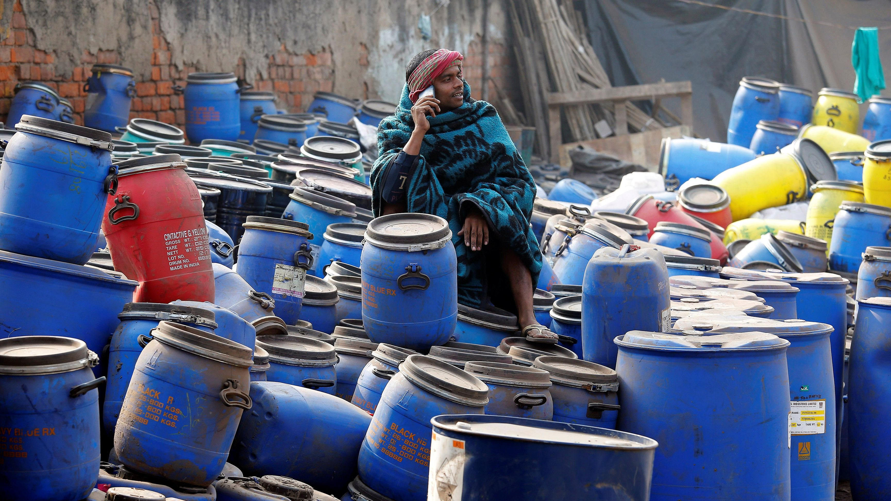 A worker speaks on his phone as he sits on chemical containers near a wholesale market on a winter morning in Kolkata, India, January 4, 2018. REUTERS/Rupak De Chowdhuri - RC11044DF6B0