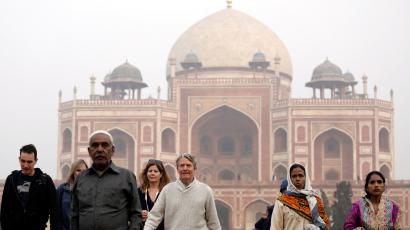 Domestic and foreign tourists walk in front of Humayun's Tomb in New Delhi