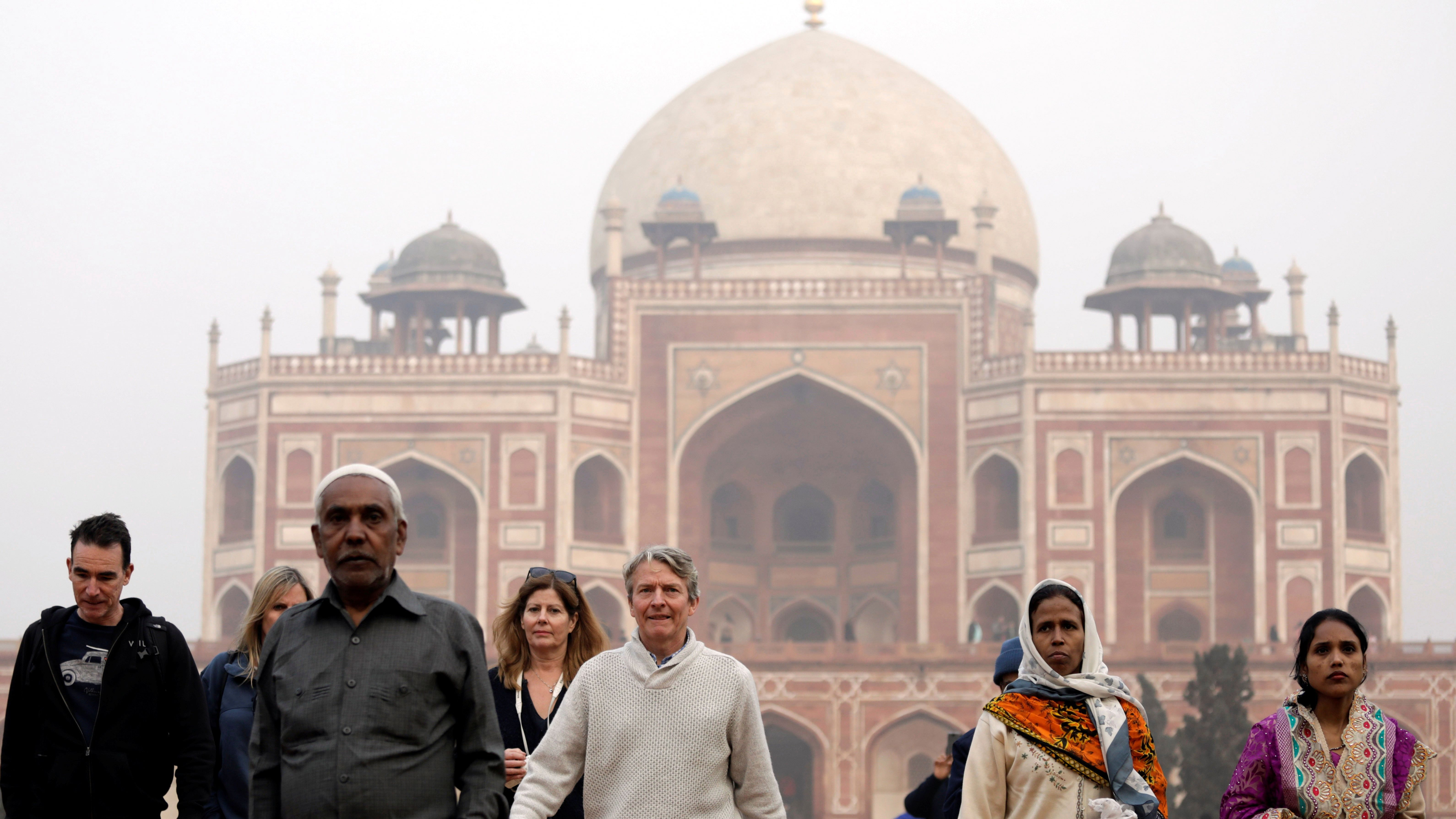 Domestic and foreign tourists walk in front of Humayun's Tomb, one of the tourist destinations in New Delhi, India, January 1, 2018. Picture taken January 1, 2018. REUTERS/Saumya Khandelwal - RC19C23785E0