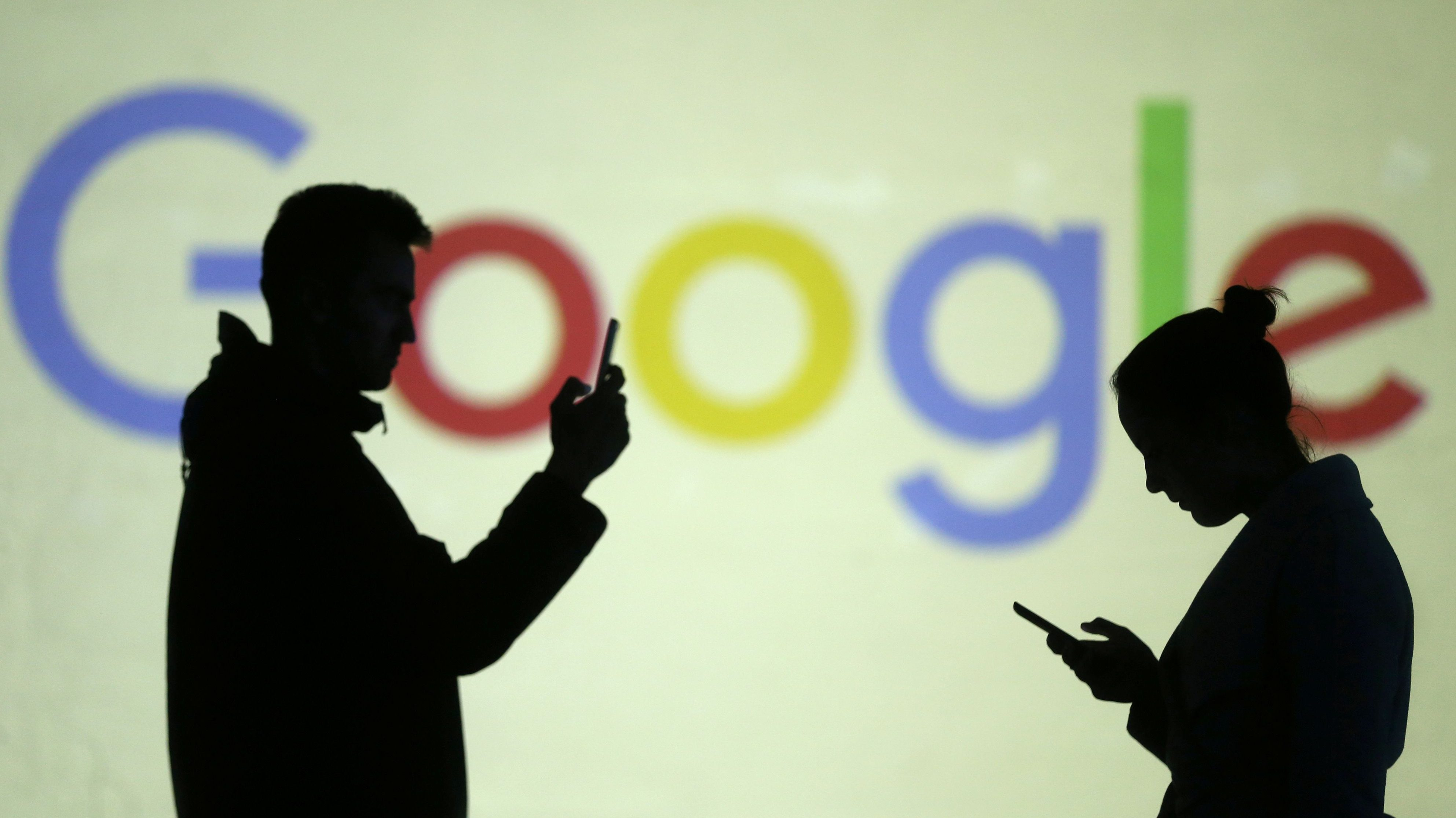 Silhouettes of mobile users are seen next to a screen projection of Google logo in this picture illustration taken March 28, 2018.
