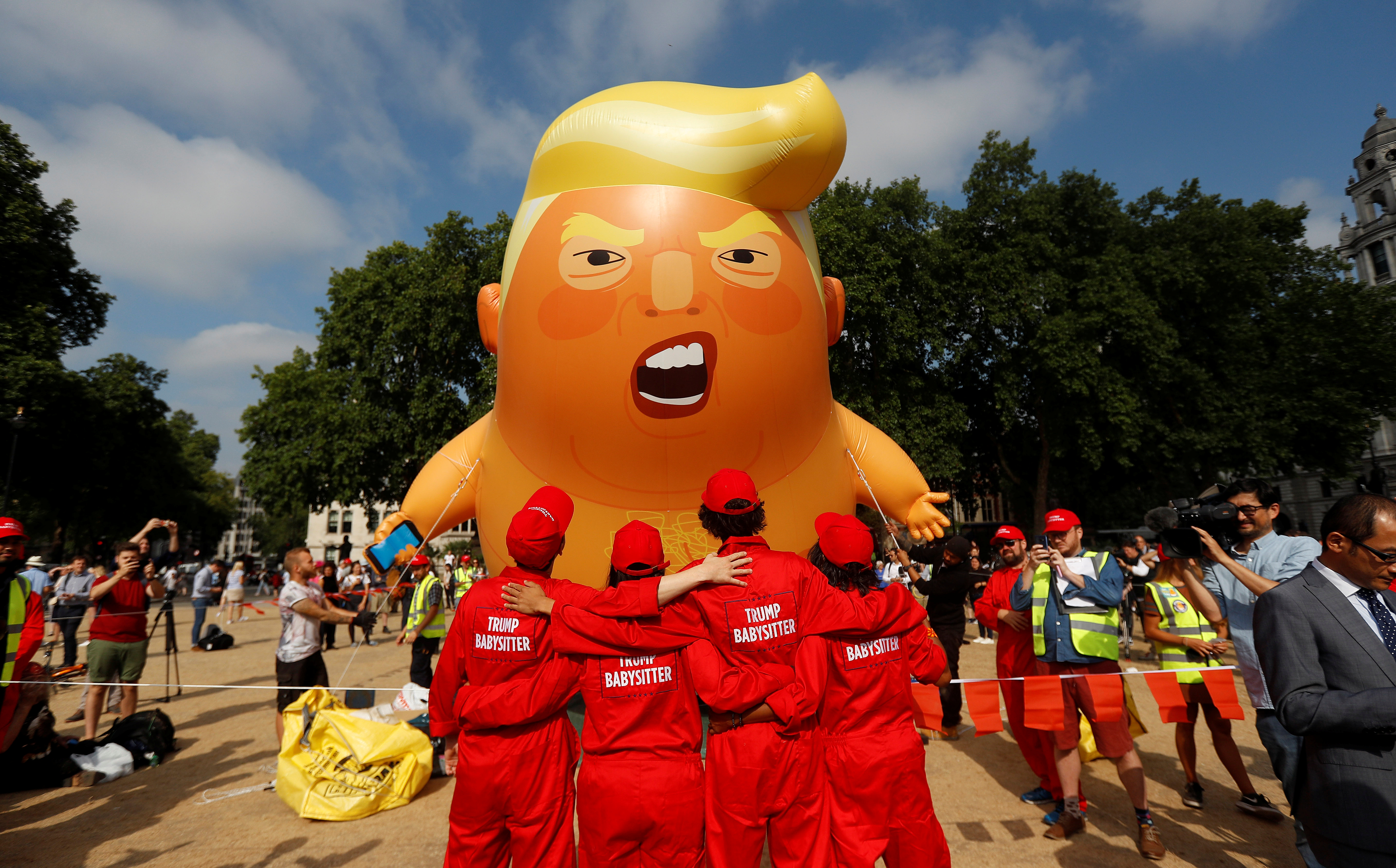 Demonstrators stand in front of a blimp portraying U.S. President Donald Trump, in Parliament Square, during the visit by Trump and First Lady Melania Trump in London, Britain July 13, 2018.