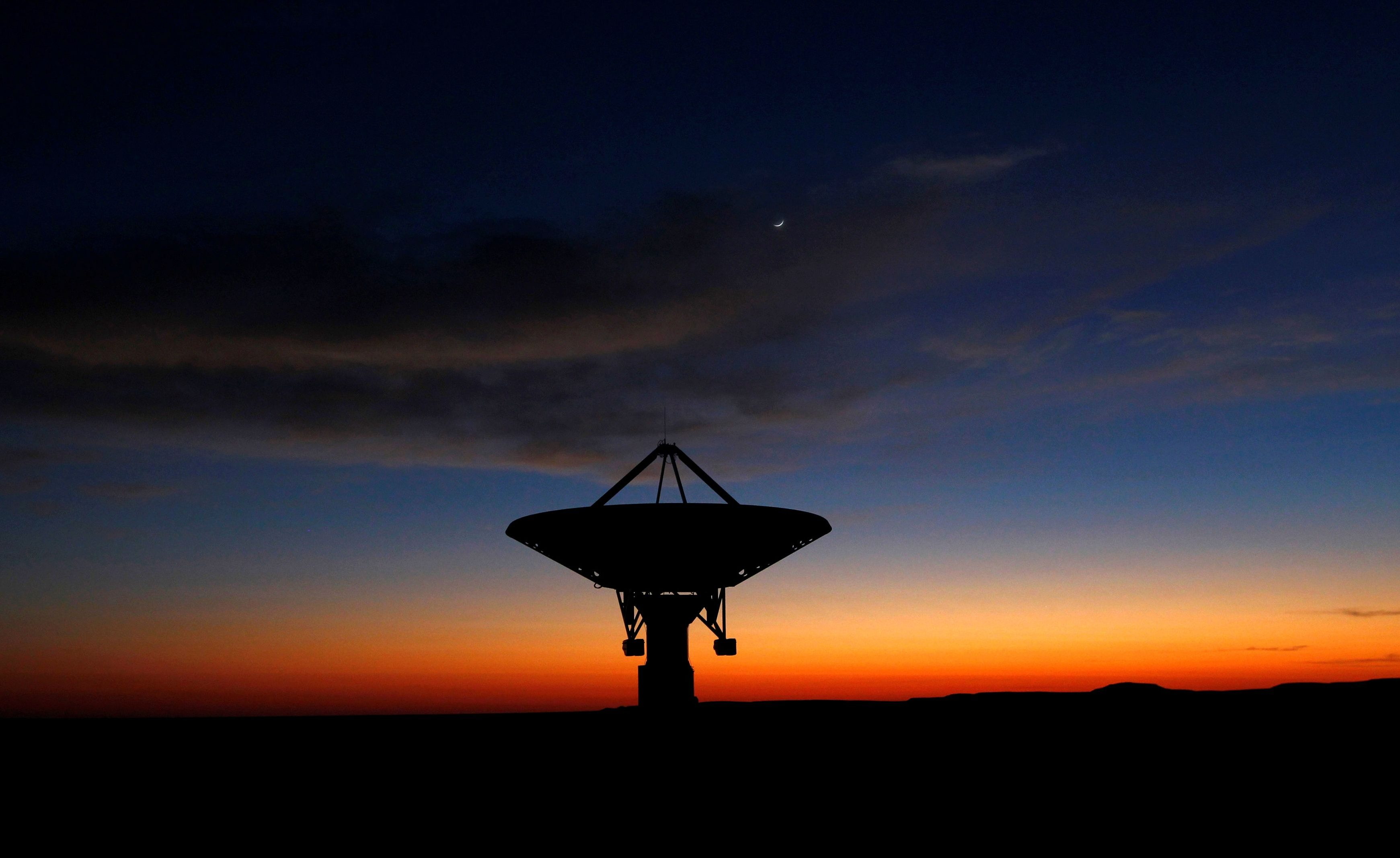 FILE PHOTO: Dawn breaks over a radio telescope dish of the KAT-7 Array pointing skyward at the proposed South African site for the Square Kilometre Array (SKA) telescope near Carnavon in the country's remote Northern Cape province