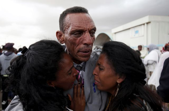 Adisalem Abu, reacts as he embraces his twin daughters, after meeting them for the first time in eighteen years, at Asmara International Airport after the Ethiopian Airlines ET314 flight arrived in Asmara, Eritrea July 18, 2018.