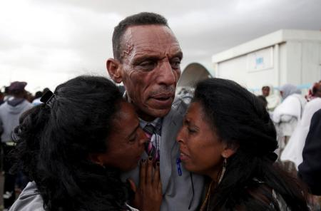 Addisalem Hadgu, reacts as he embraces his daughters, after meeting them for the first time in eighteen years, at Asmara International Airport after Ethiopian Airlines ET314 flight arrived in Asmara, Eritrea July 18, 2018.