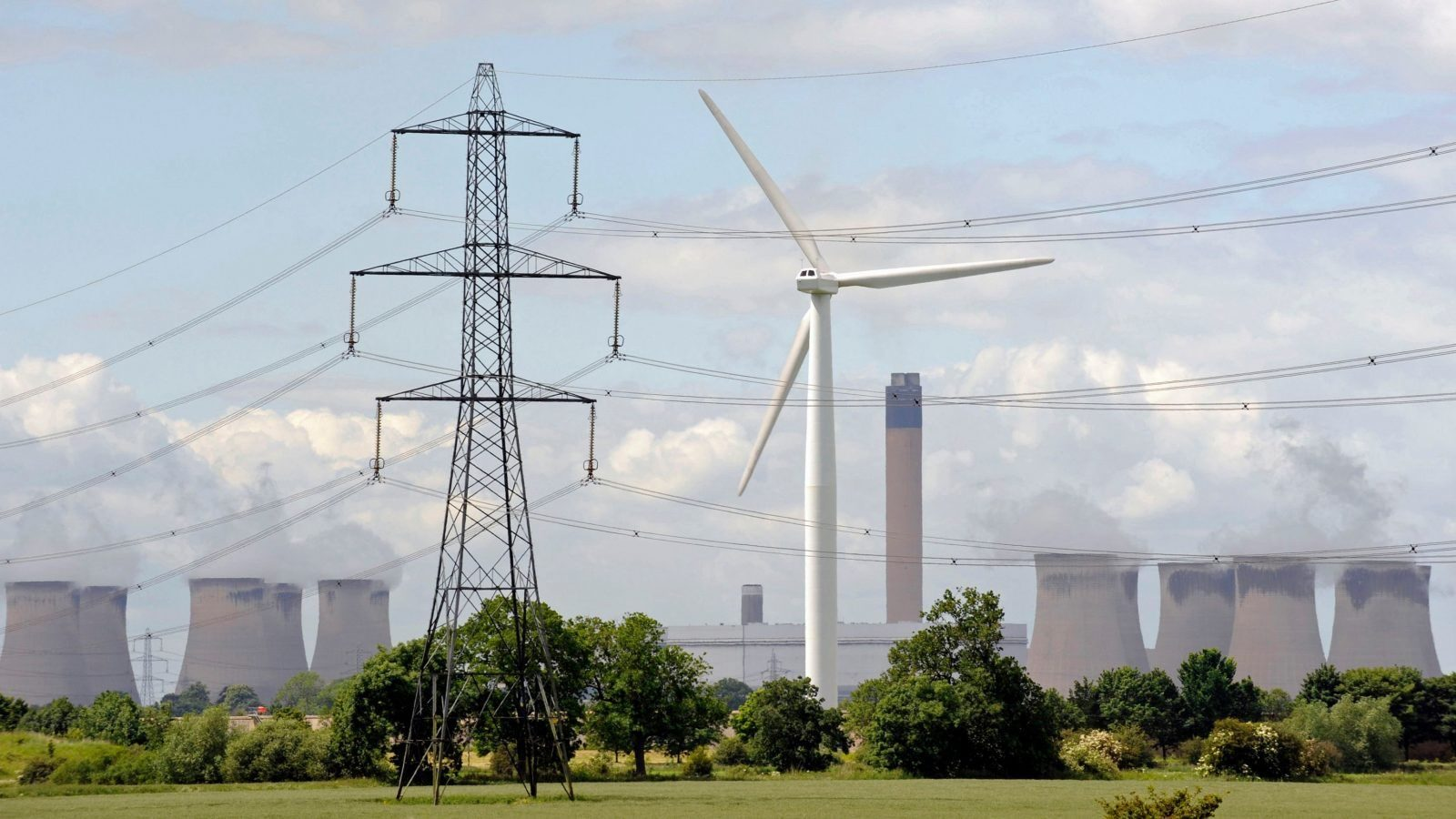 """A wind turbine is pictured at Loftsome Bridge Treatment Works, in front of Drax Power Station near Selby, northern England, June 19, 2008.   As many as a quarter of British homes could be fitted with solar heating systems and thousands of wind turbines erected across the country under government plans for a """"green revolution"""" to be set out around June 28, 2008.  Photo taken June 19, 2008.      REUTERS/Nigel Roddis    (BRITAIN) - GM1E46L1H0301"""