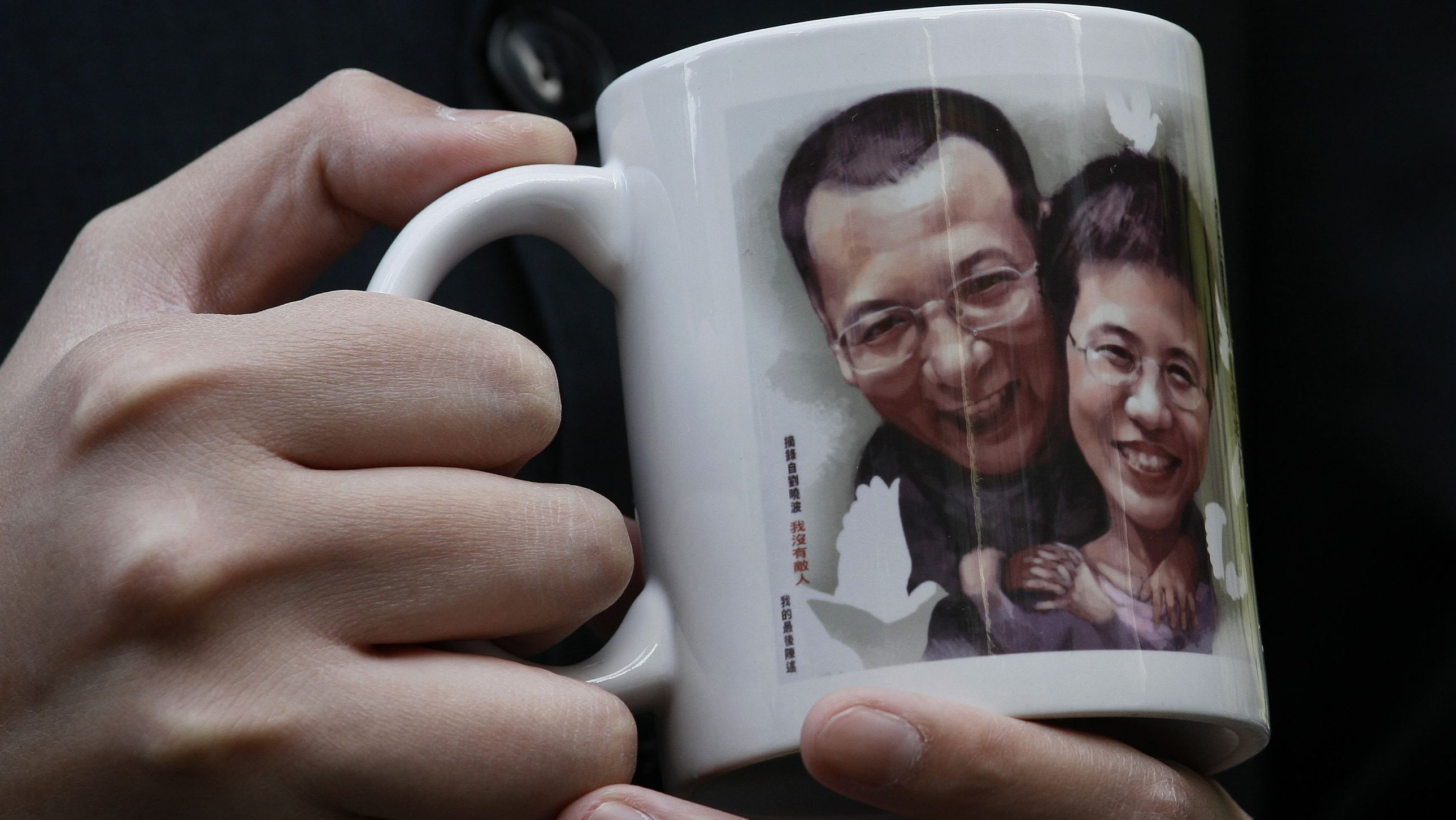 A protester holds a mug featuring an image of jailed Chinese dissident Liu Xiaobo and his wife Liu Xia outside Hong Kong's Legislative Council December 8, 2010, before several lawmakers leave for Oslo to attend the Nobel Prize presentation ceremony. China is conducting a sweeping crackdown on dissent ahead of this week's awarding of the Nobel Peace Prize to jailed dissident Liu Xiaobo, casting the net wide to prevent friends and family attending.   REUTERS/Bobby Yip   (CHINA - Tags: POLITICS) - GM1E6C817NX01