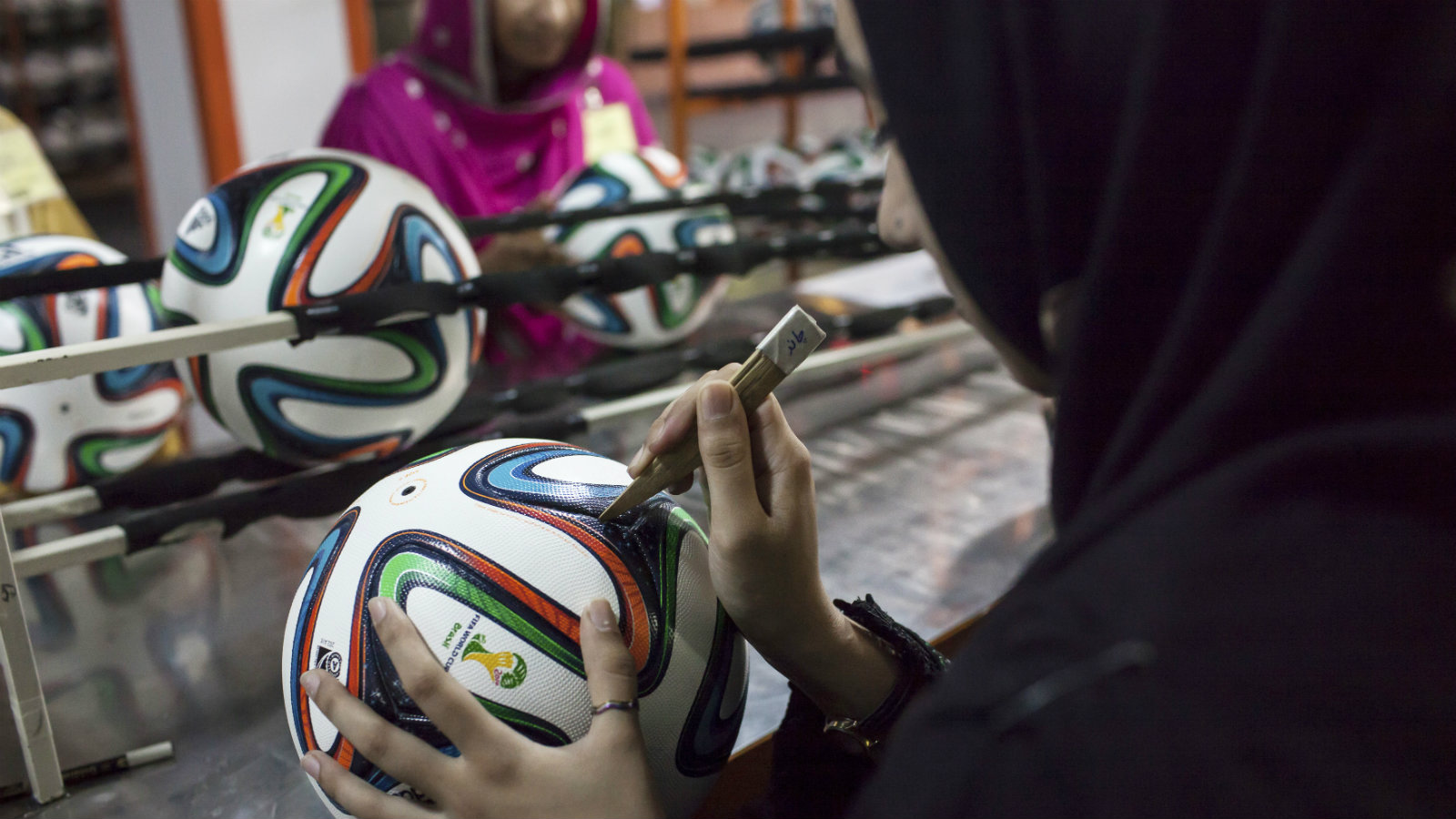 An employee conducts the final check to fix any cavity in the seams of a ball inside the soccer ball factory that produces official match balls for the 2014 World Cup in Brazil, in Sialkot, Punjab province May 16, 2014. It was when he felt the roar of the crowd at the 2006 World Cup in Germany that Pakistani factory owner Khawaja Akhtar first dreamt up a goal of his own: to manufacture the ball for the biggest soccer tournament on the planet. Last year he finally got his chance - but only 33 days to make it happen. Picture taken May 16.