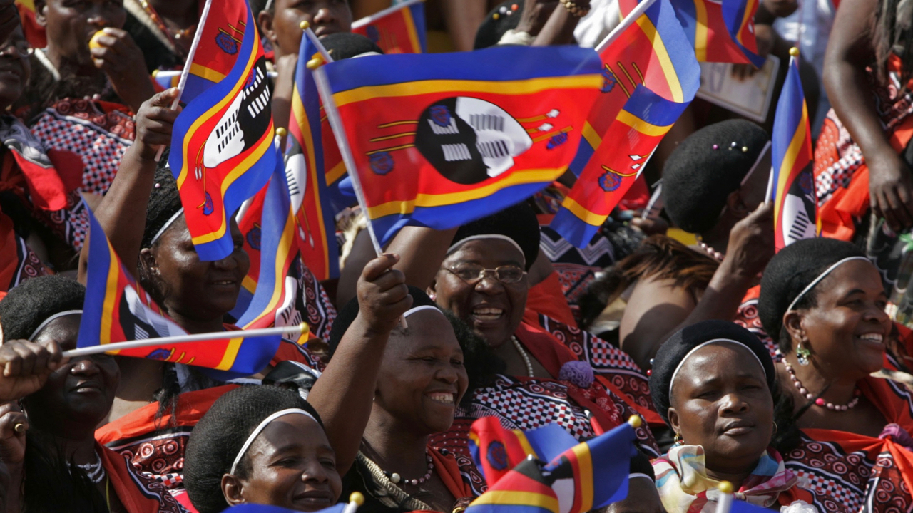 People wave the National flag of Swaziland, during the birthday celebrations of the Swaziland King Mswati III, on the outskirts of the city of  Mbabane, Swaziland, Saturday, Sept. 6, 2008. The Swazi king entered a stadium in an open-topped BMW to cheers and flag-waving Saturday, marking his 40th birthday and his country's 40th independence anniversary. (AP Photo/Schalk van Zuydam)